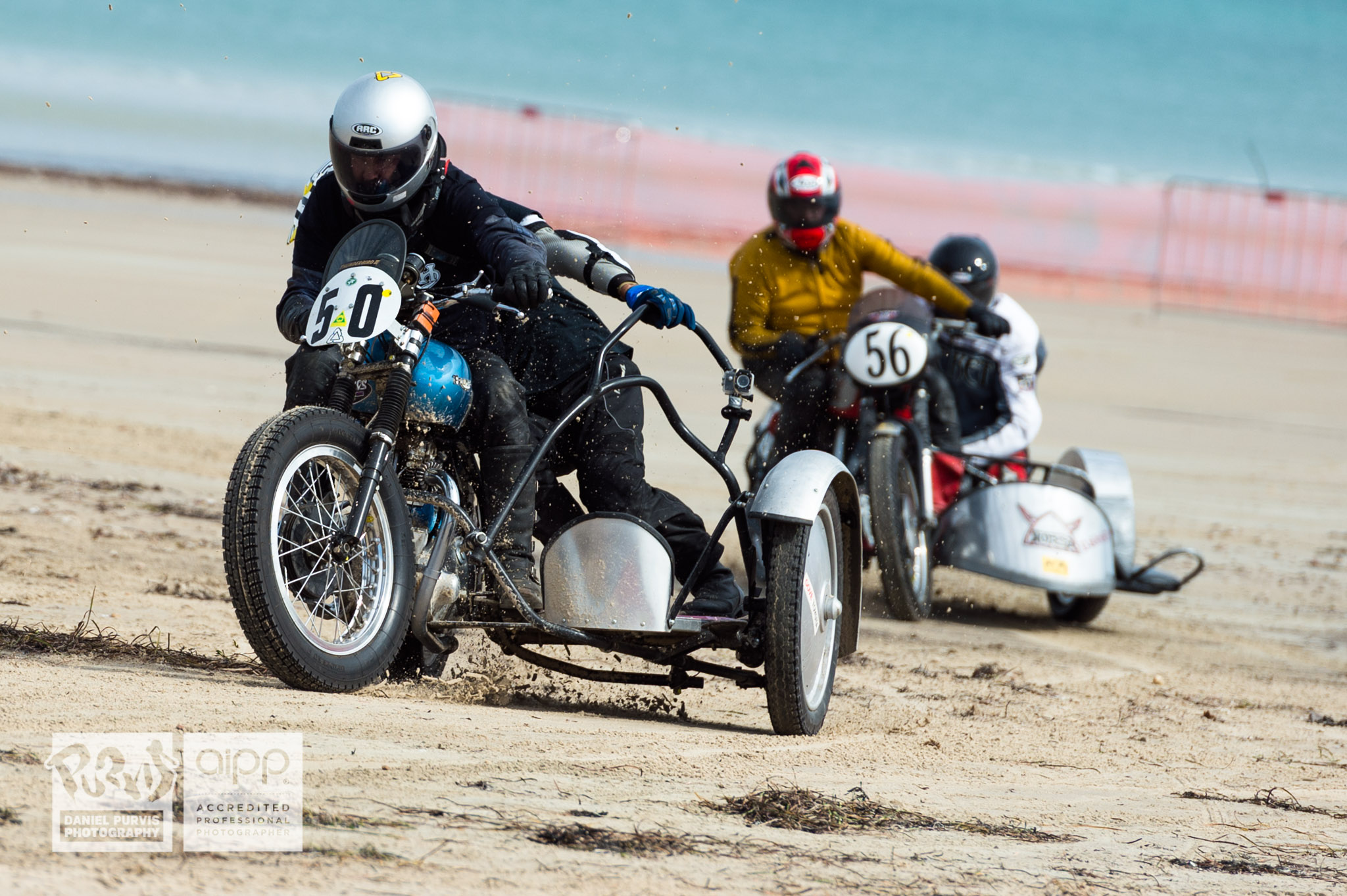 (50) Paul Dempsey / Carey Dechamps riding 1950 Triumph chased by (56) David Sigston / Vince Hitchman riding 1956 Norton/BSA, rounding final corner. © Daniel Purvis