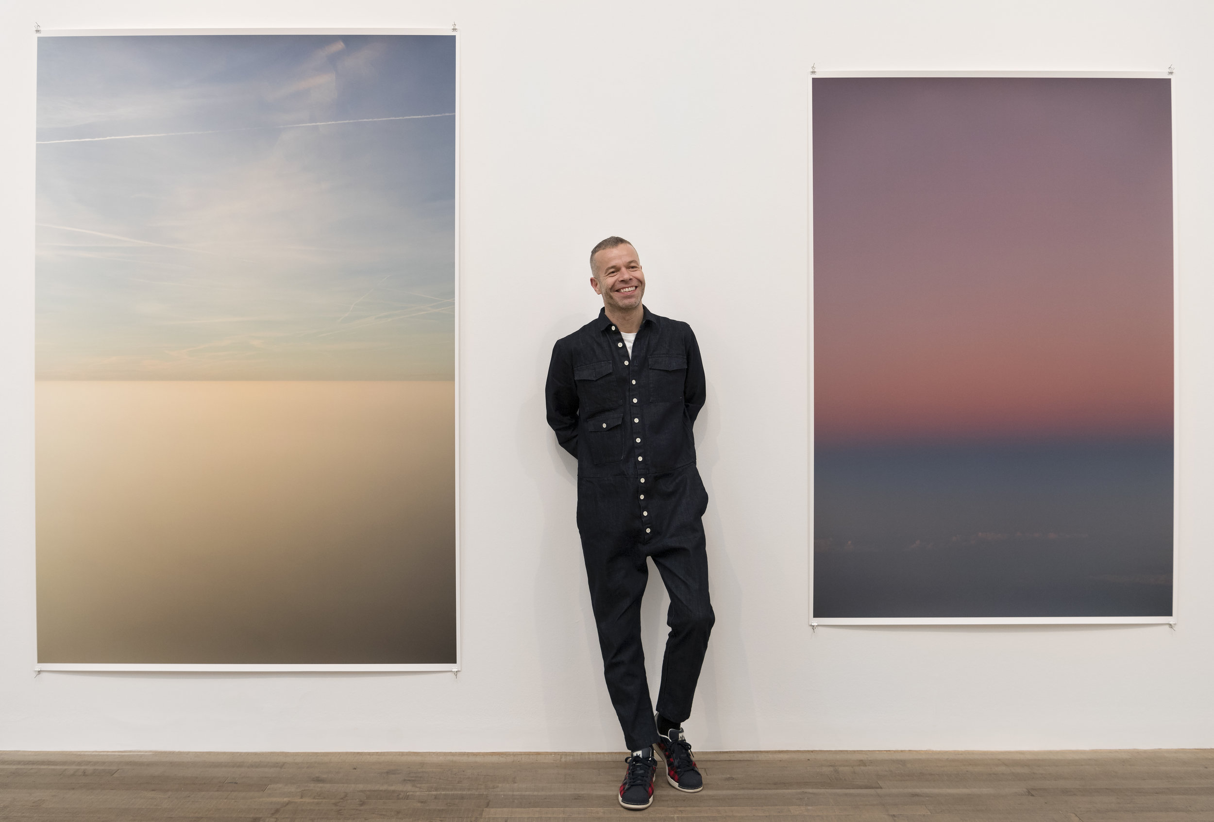 Wolfgang Tillmans poses in front of his works  Transient 2,  2015 and  Tag/Nacht II,  2010. Courtesy Tate Photography