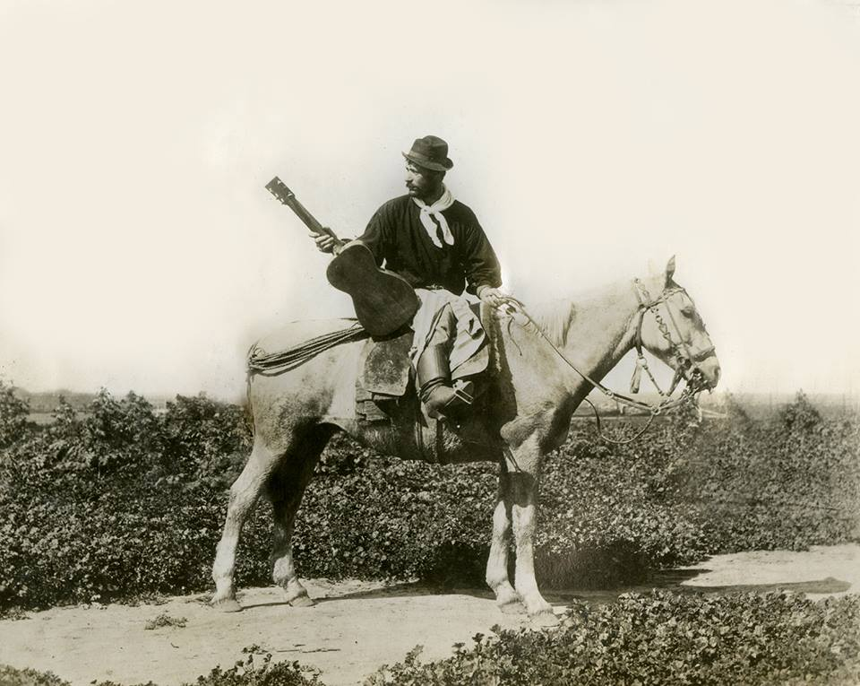 "Argentine ""payador"" Juan Arroyo with his guitar and horse c1870."