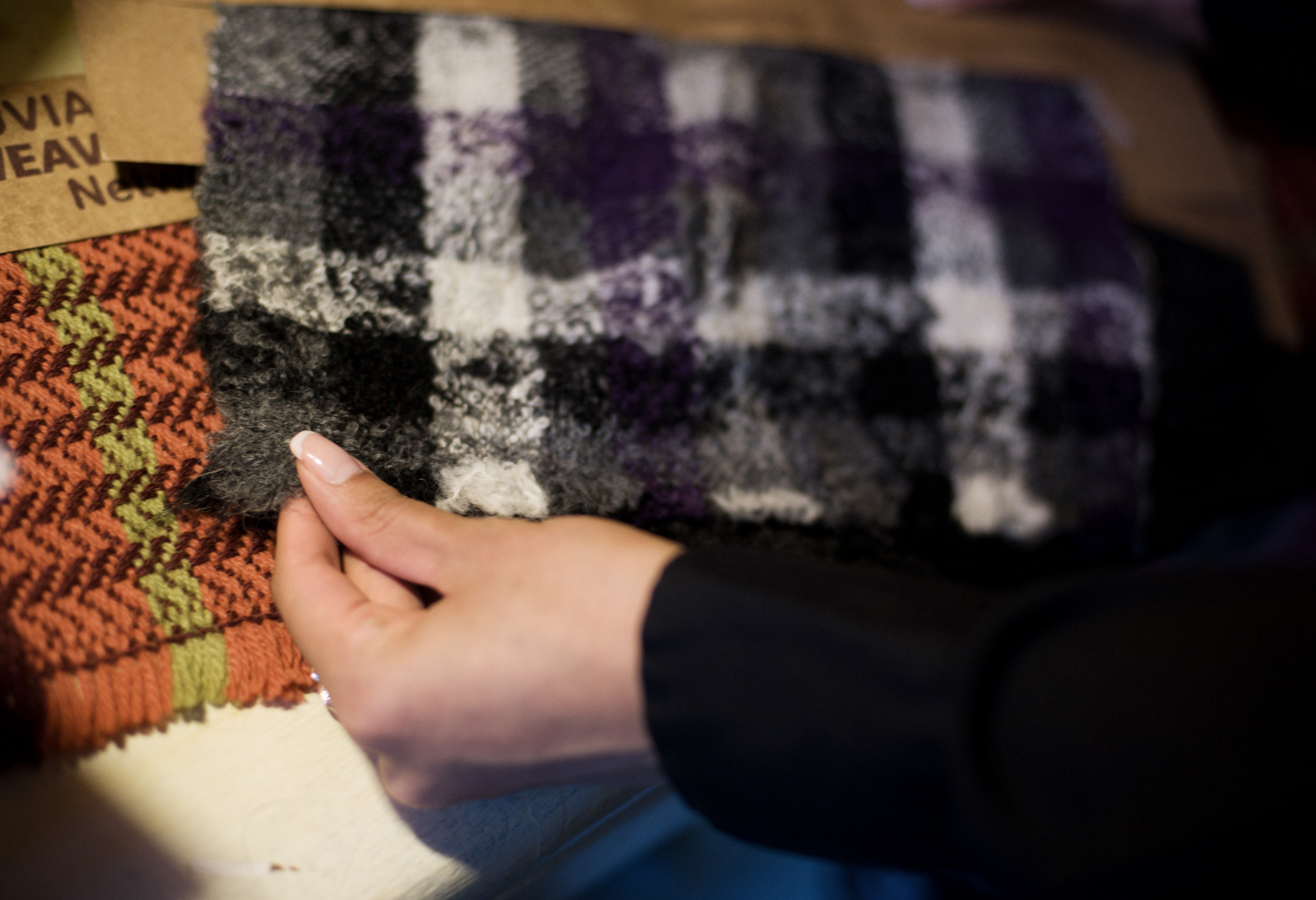 Benita tests the hand of one of the Peruvian textiles recently brought back from a sourcing trip.