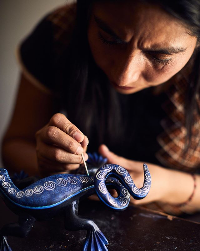 Cris painting an Alebrije. Not only does she carve and paint, she teaches classes as well.