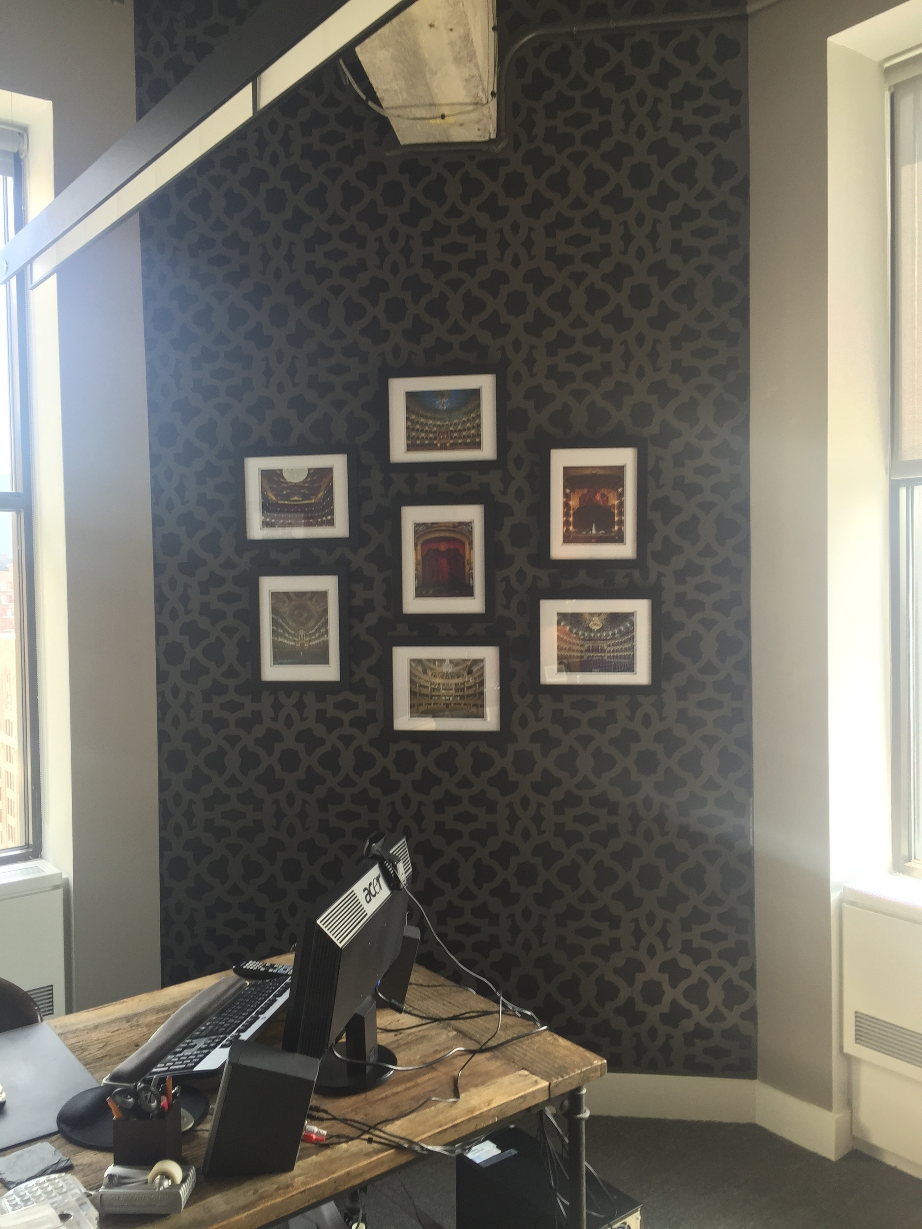 Stencils also create interesting palates for displaying art work or gallery walls. Here, we brought the eye to the high ceilings and created a real focal point for this masculine corner office.