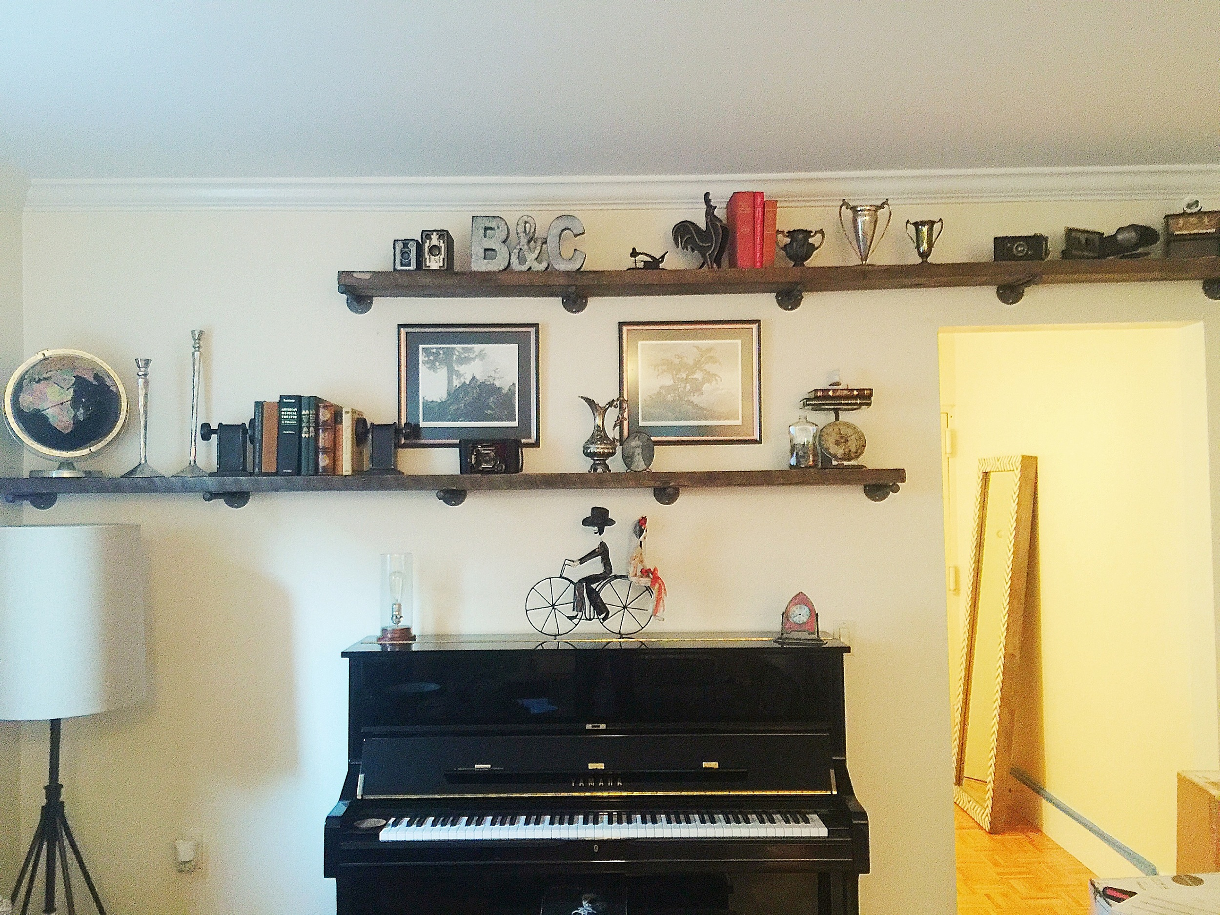 Space above the floor lamp and doorway was used to bring the focus in this area up above the piano for a cool eclectic look.