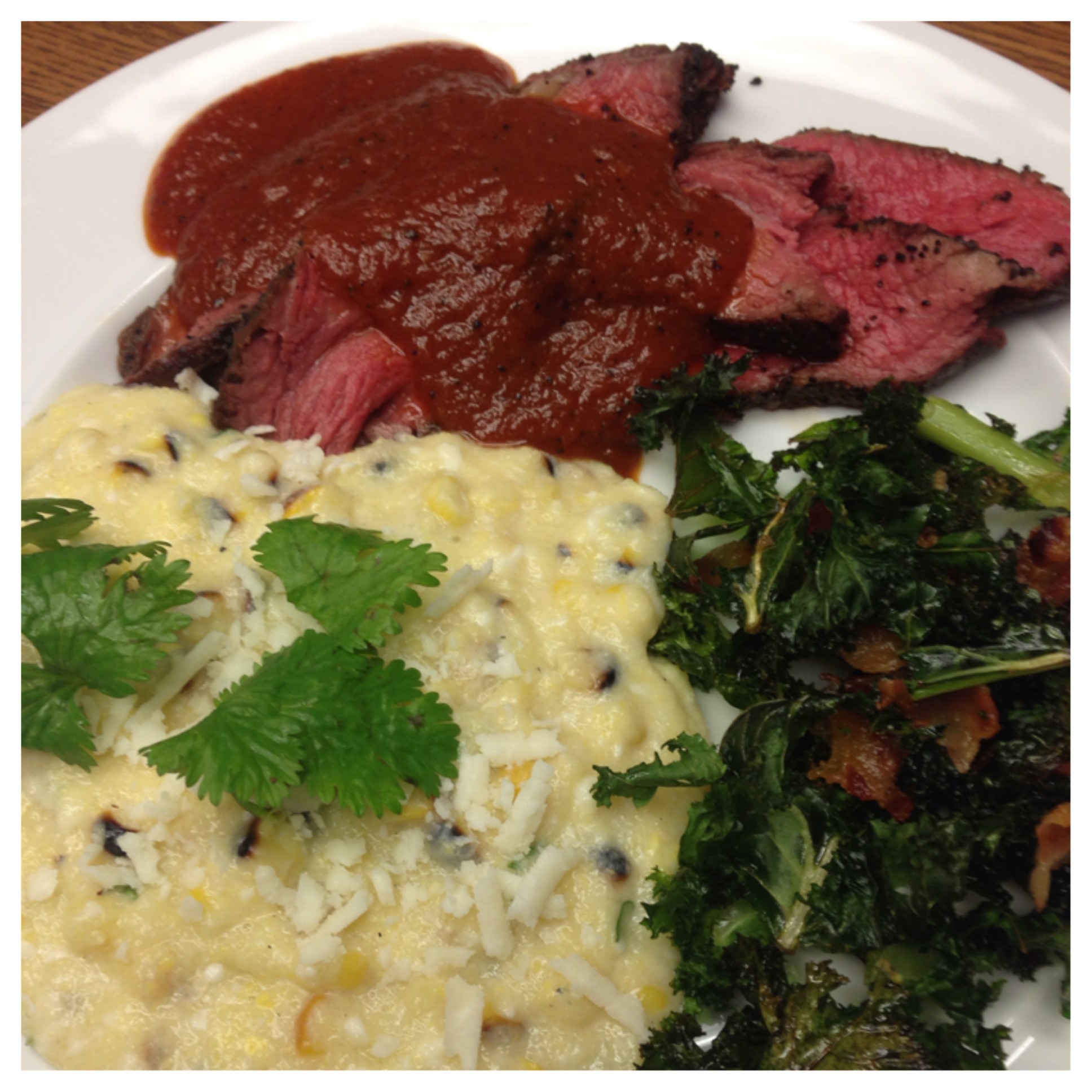 I SERVED THE STEAK WITH A SIDE OF MEXICAN CORN POLENTA AND KALE CHIPS WITH BACON. I TOOK INFLUENCE FROM AMERICAN BARBECUE, MEXICAN AND ITALIAN CUISINES. THE POLENTA HAS COCONUT MILK FOR SWEETNESS, ROASTED CORN, CILANTRO, LIME JUICE AND COTIJA CHEESE,ALL THE FLAVORS OFTHE POPULAR MEXICAN STREET FOOD. THE KALE IS A PLAY ON SOUTHERN GREENS THAT ARE USUALLY MADE WITH COLLARDS. I WANTED A CRUNCHY TEXTURE IN THE DISH SO I MADE THEM INTO CHIPS AND ADDED BACON INSTEAD OF THE SMOKED HAM HOCK WHICH IS TYPICALLY FOUND IN GREENS.