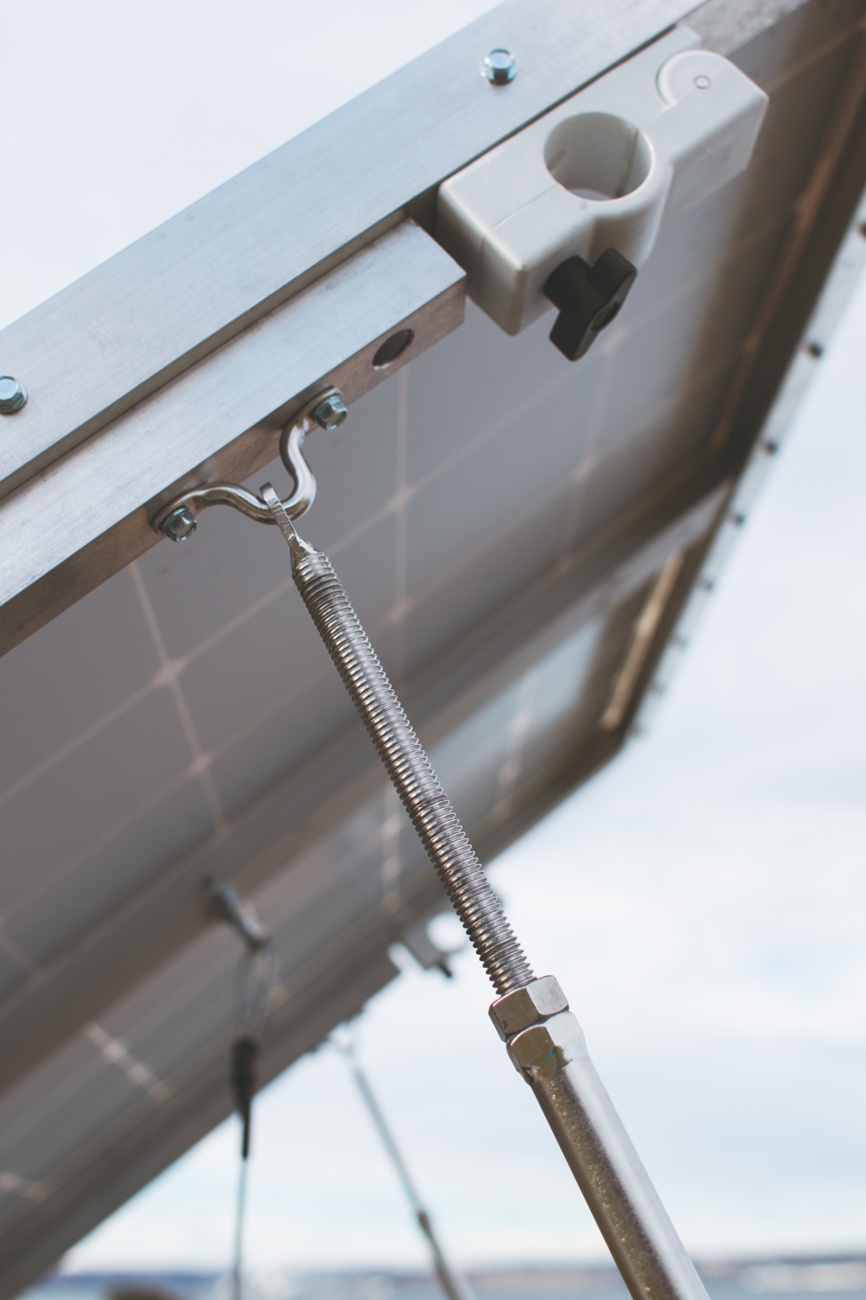 The white clip in this photo is the locking mechanism for the system. When the black toggle is screwed out, the lock opens and can be clamped over the cross beams on the roof rack.