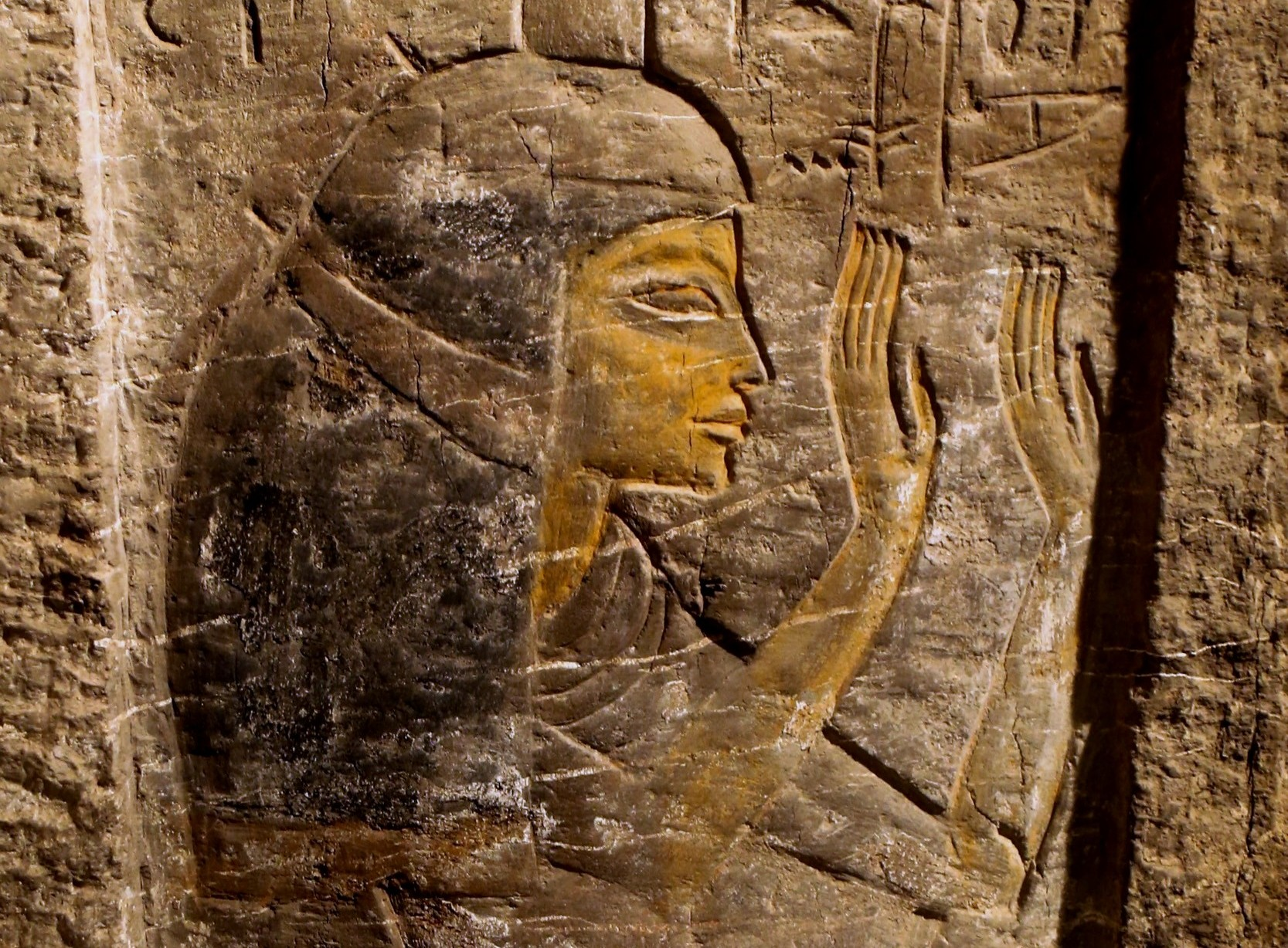 This image shows Maia wearing a heavy wig and with her hands raised in adoration. From a rock-cut pillar in her tomb.