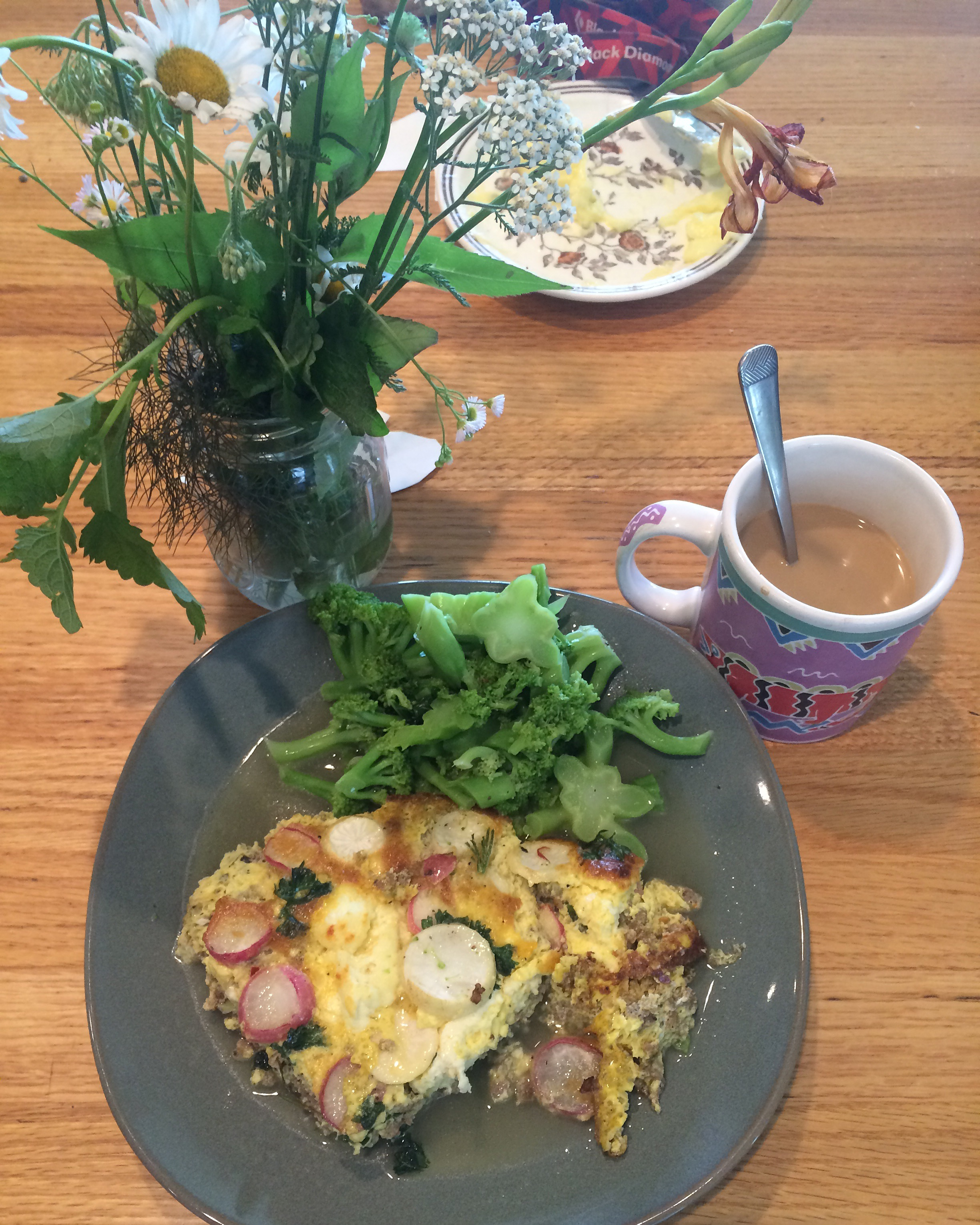 The non-vegetarian frittata I made with pork sausage, homemade cheese, garlic scapes, radishes, turnips, and parsley with steamed broccoli and butter.