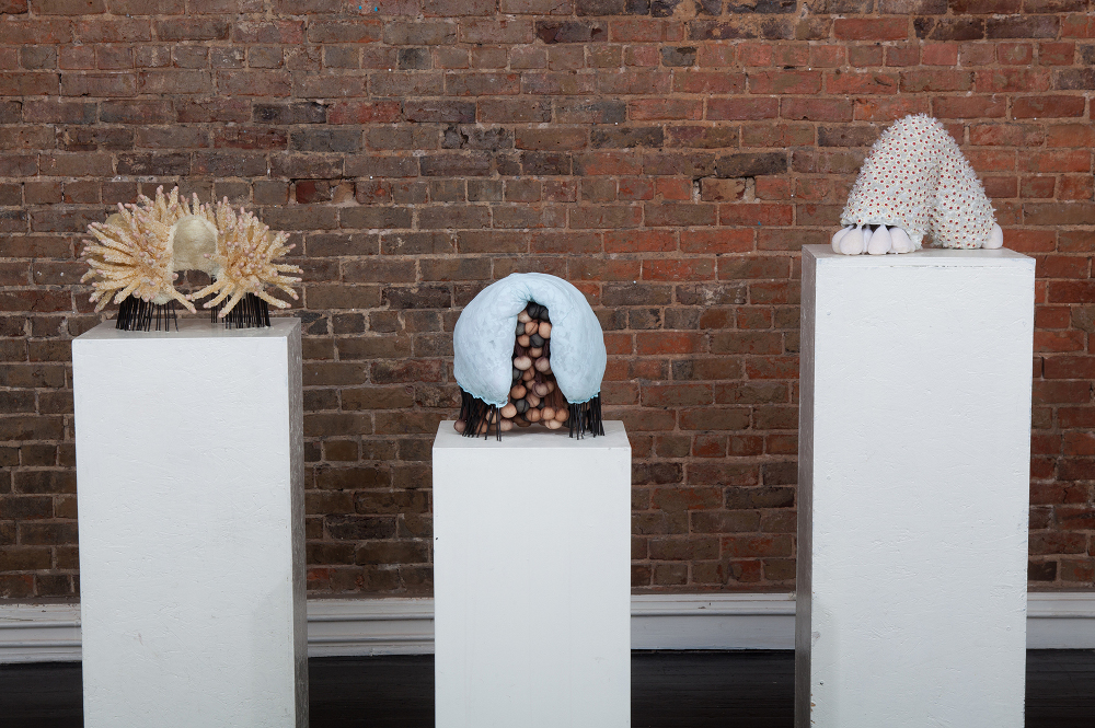 "This image includes three sculptures (listed in order from left to right):  An Iceberg Between the Shoulder Blades (Defense), An Iceberg Between the Shoulder Blades (Burdens), &   Broken Bone Kaleidoscope  (2015) ear plugs, cocktail straws, latex tubing, bath loofahs, nylon stockings, rice, pillow stuffing, lace camisole, bath mats, pencil erasers, pasta, salt, plastic spoons 20"" x 62"" x 14"" * Titles borrowed from the poems, When Death Comes, by Mary Oliver and Poem for Miss Meade, by Rachel McKibbens."