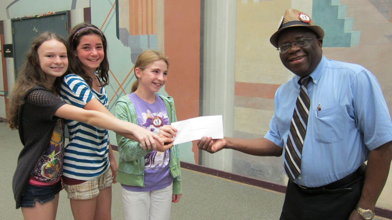 Clara Tazelaar, Ella Nadeau, and Maddy Peel present Dr. Daniel Shungu of United Front Against Riverblindness with a check for $350 to help battle the devastating disease that affects many adults in Africa.