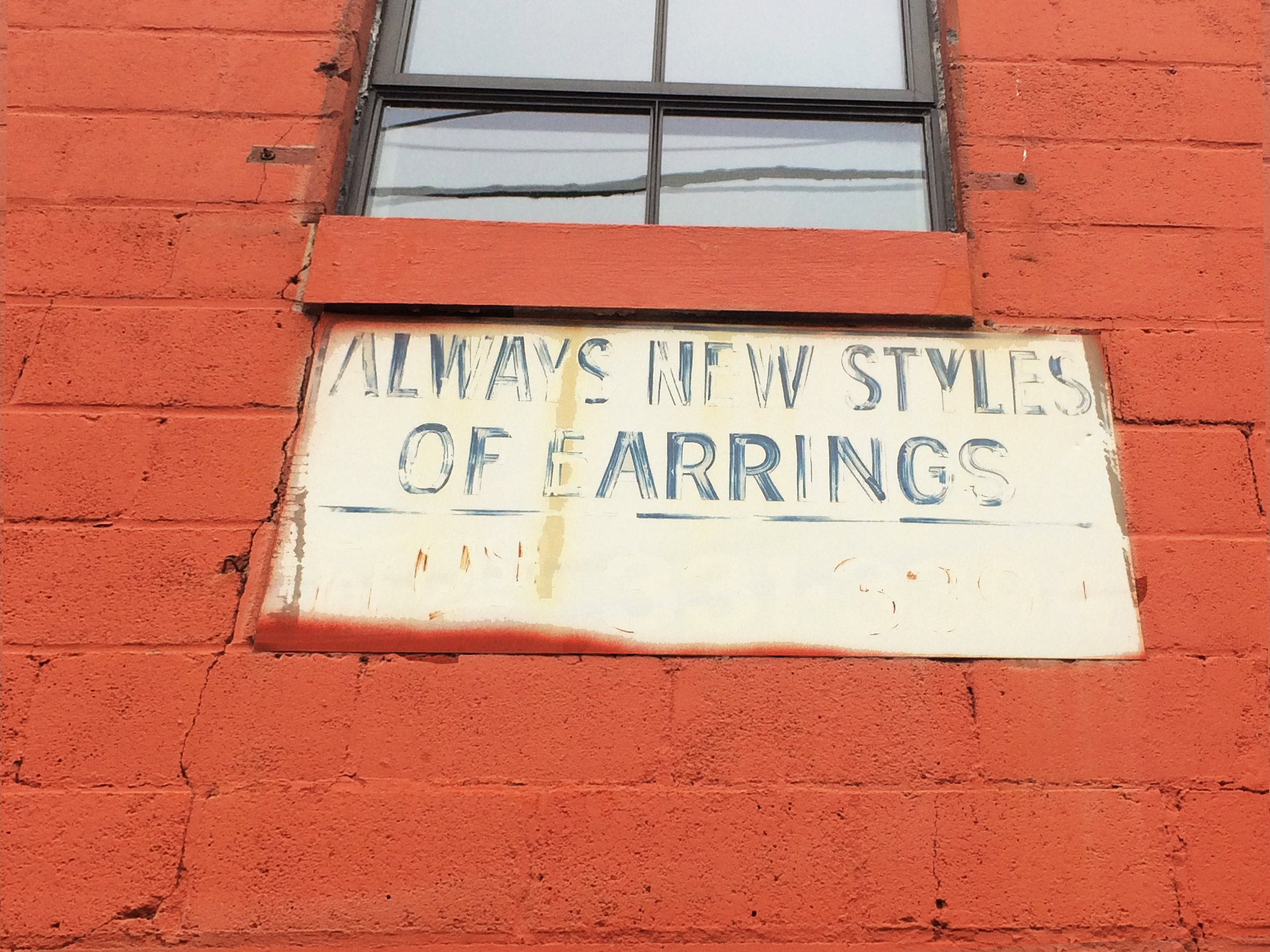 """ALWAYS NEW STYLES OF EARRINGS"" Still reads on one of the walls from the time the buidling was a storage for costume jewelry, a testament to its layered history"