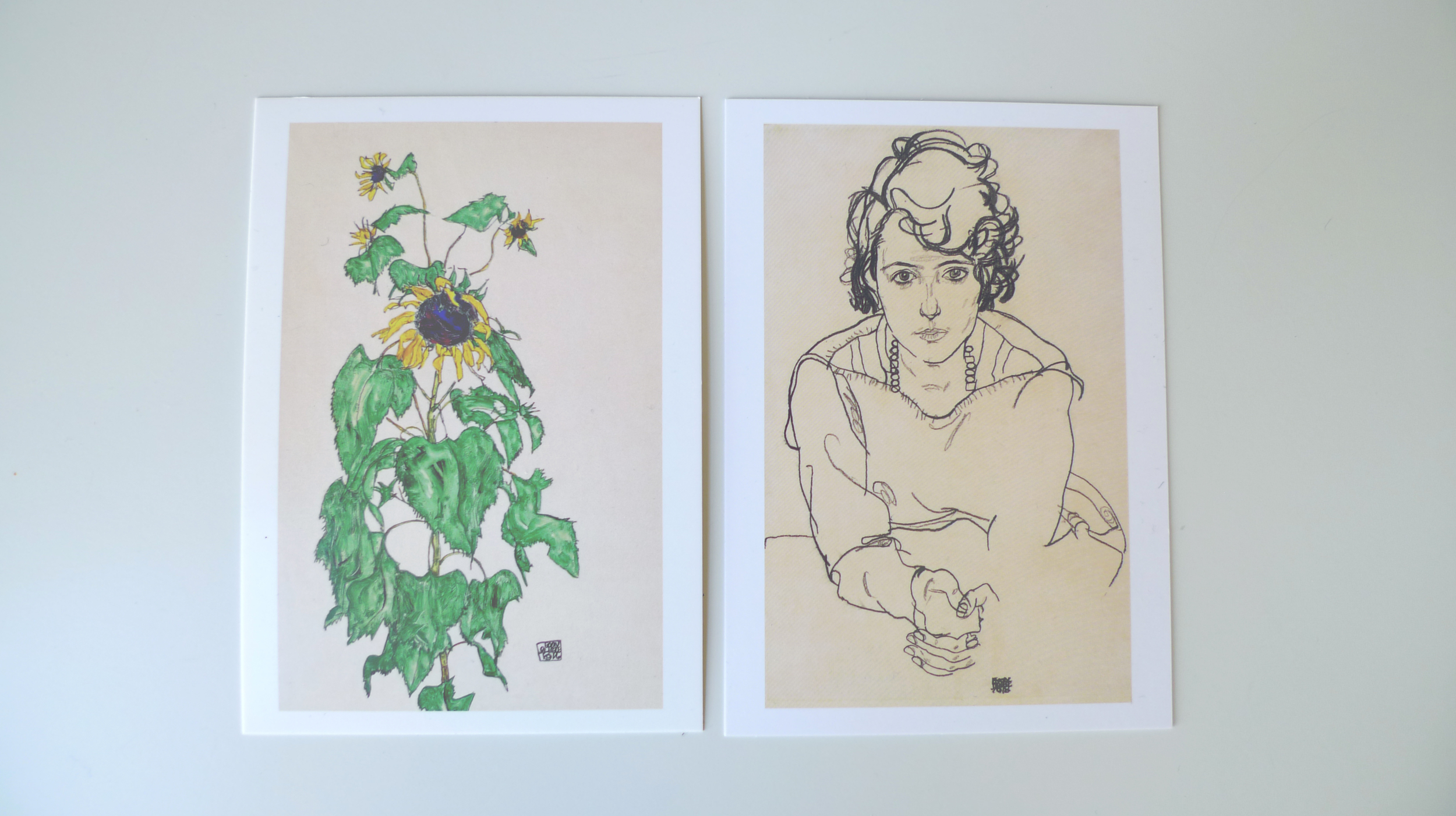 Two Egon Schiele postcards from the Neue Galerie shop: Sunflower, 1916 (left) andSeated Woman, 1918 (right)