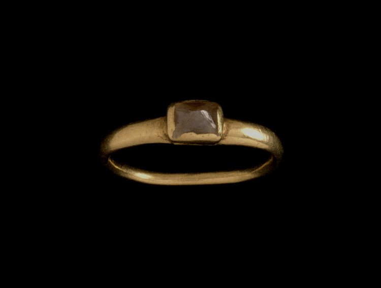 Gold finger-ring:thin rounded hoop, slightly expanding upwards with a rough brown diamond. 3rd C Roman. The British Museum Collection.