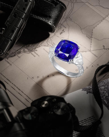A Fine Natural Sapphire and Diamond Ring. The cushion-shaped sapphire, weighing 10.83 carats, between heart-shaped diamond shoulders, the gallery and hoop pavé-set with brilliant-cut diamonds, diamonds approximately 3.05 carats total, ring size 6½