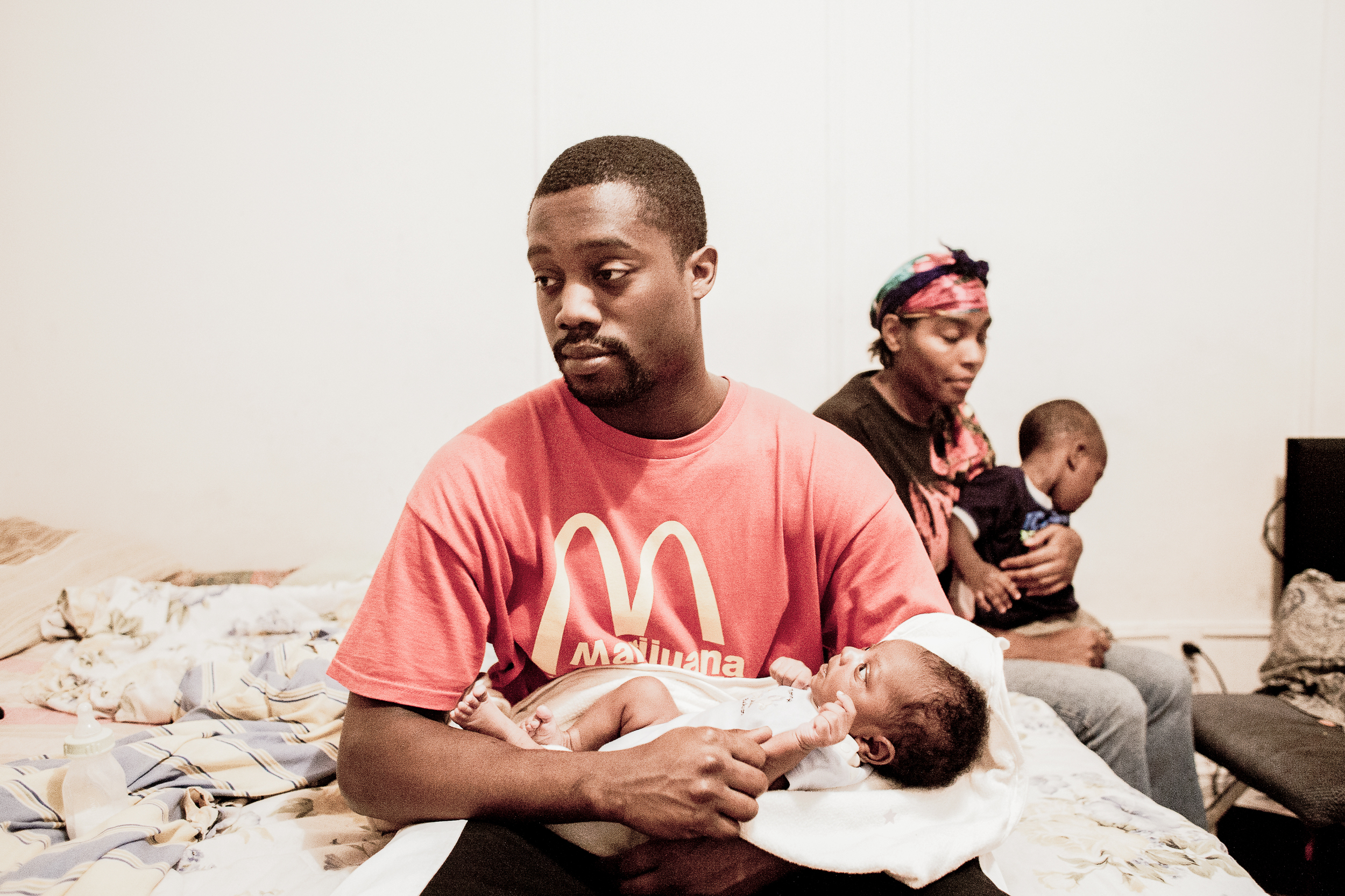 The father of Roberta's newborn son holds his baby, 2010.