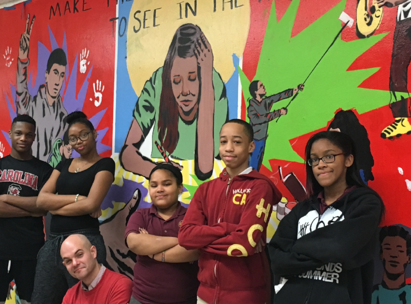 Youth Artists at the East Fordham Academy For the Arts stand in front of their mural, 2016