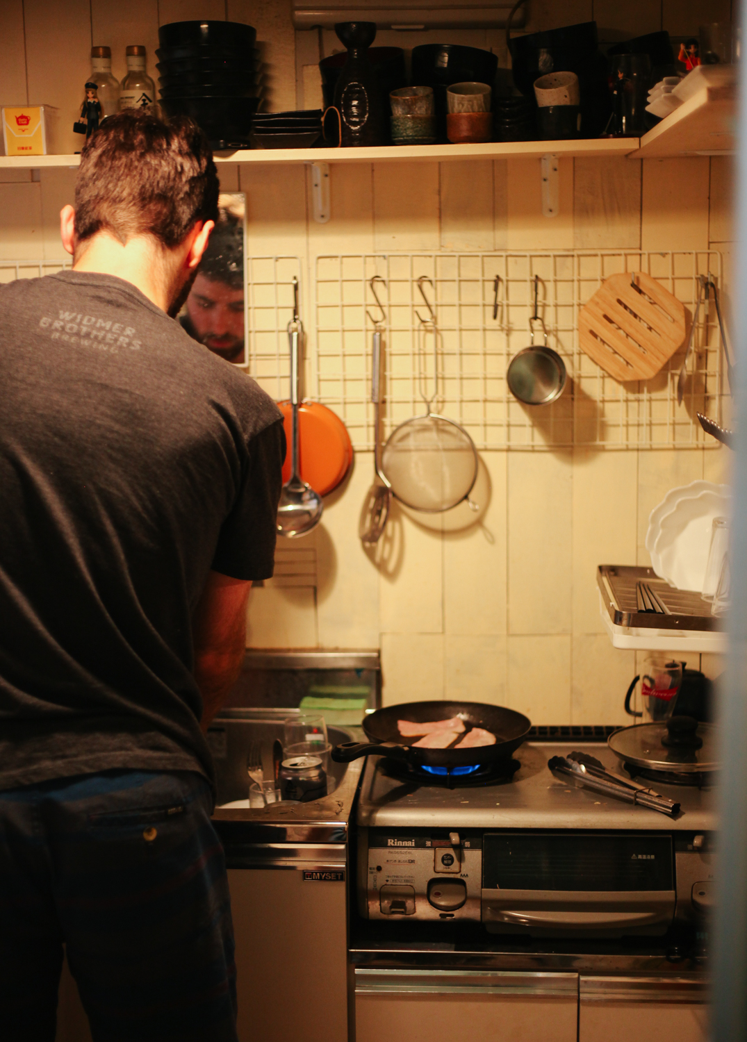 Zac making bacon in our one-burner kitchen at Riki's house.