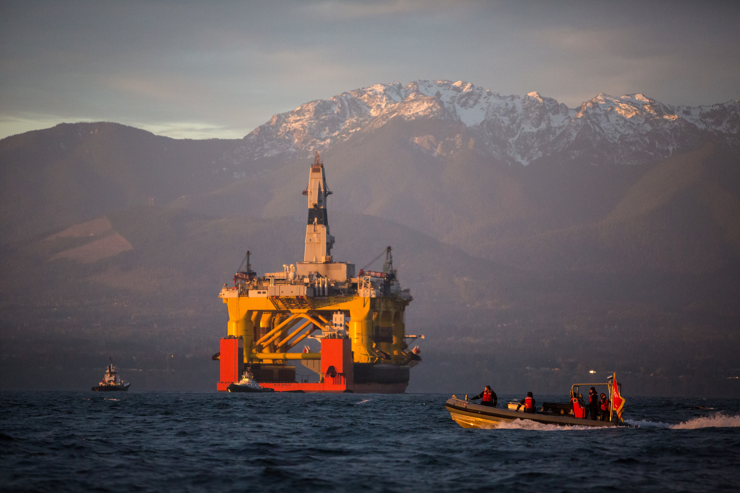 With the Olympic Mountains in the background, a Greenpeace boat crosses in front of the Transocean Polar Pioneer as it arrives in Port Angeles, Washington on its way to Seattle. The rig arrived aboard a transport ship after traveling across the Pacific before its eventual Arctic destination.