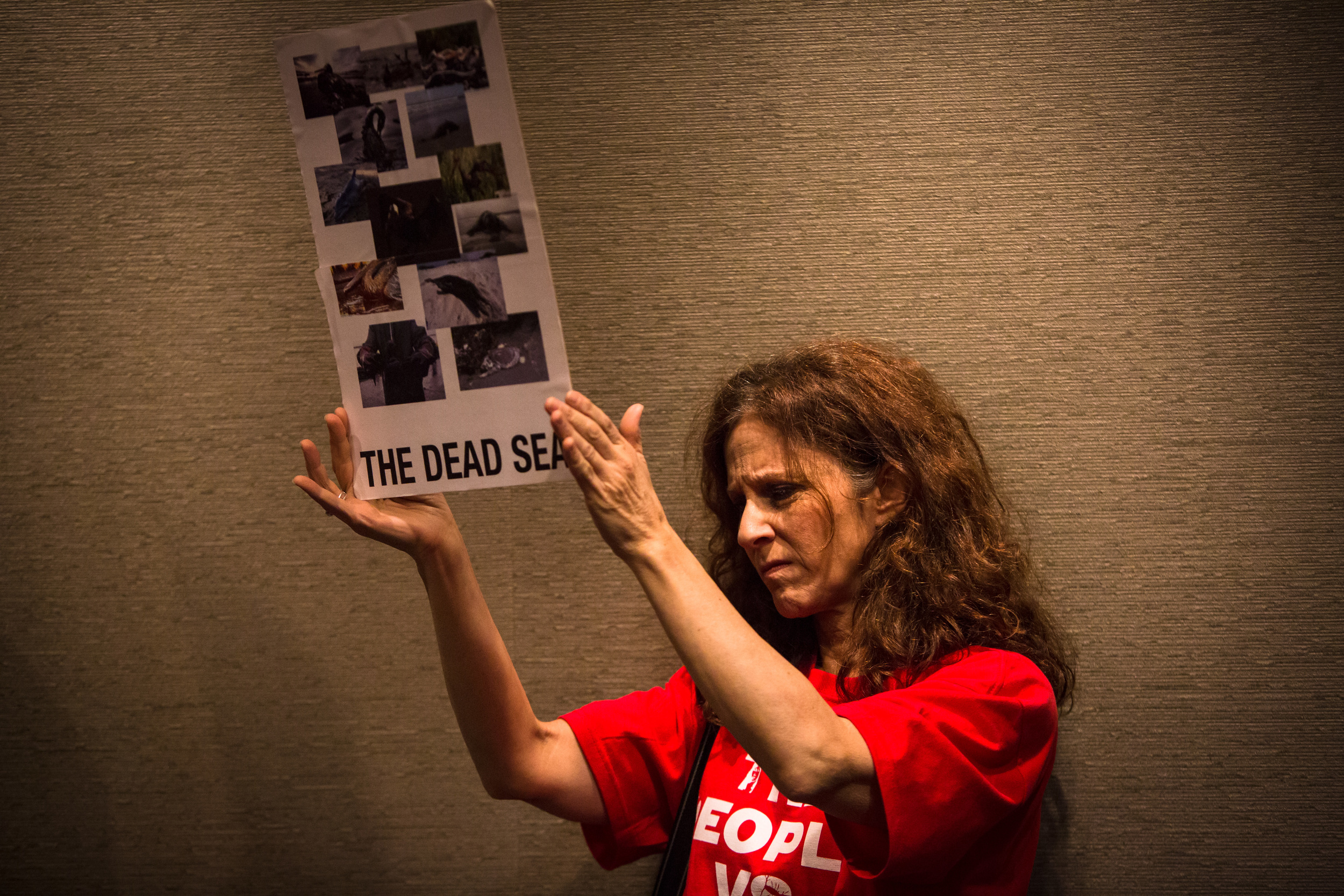 Marla Katz holds up a photos from the BP oil spill in protest of Shell's oil rig coming to Seattle during a meeting at the Port of Seattle on Tuesday, May 12, 2015. Members of the community packed in to speak to the Port Commissioners before they vote on whether to allow the rig to come to port.