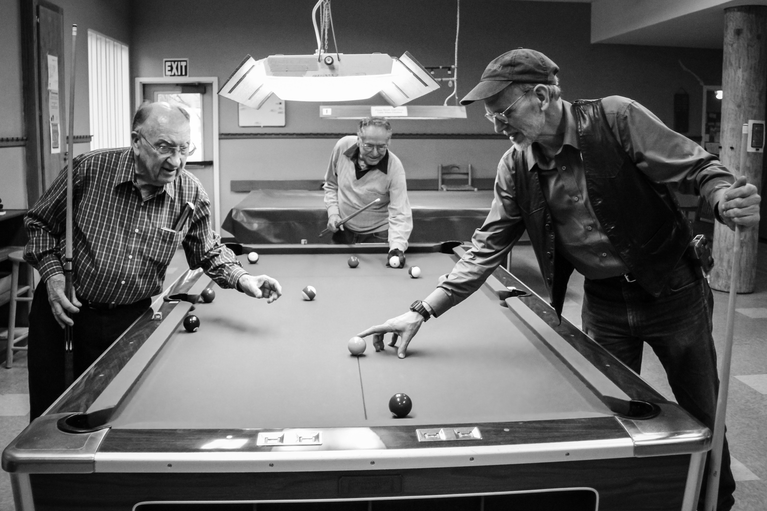 """Bob Souders, Ira Webber and Dr. Robin Rieck arrange the balls on the table during a game of pool at the senior center. Each one regularly plays with other members for a few days each week. Rieck, a former professor of business at Western Washington University, also occasionally teaches classes at the center. His most recent class was """"The Magic on How Societies Create and Lose Wealth."""""""