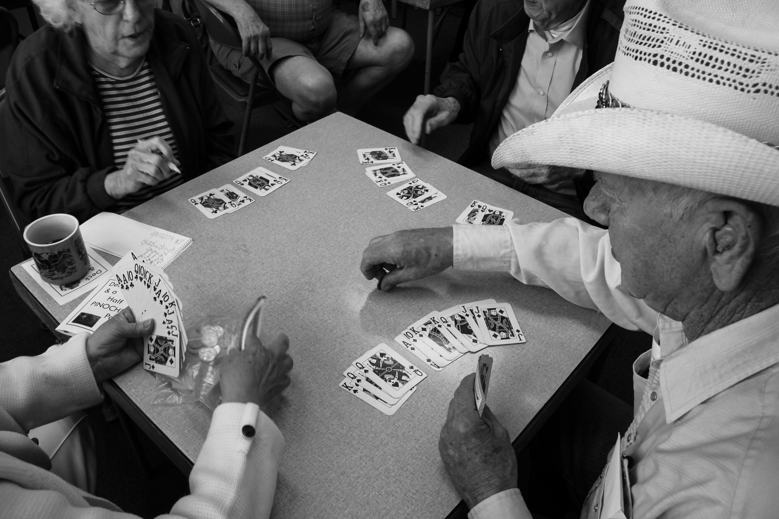 """Raymond Snook dons a cowboy hat while playing a game of Pinochle with Ralph Carmichael and other members at the senior center. """"They call me Cowboy,"""" Snook said. The Pinochle players laugh and crack jokes as they play a few hands every Monday, Wednesday and Friday."""