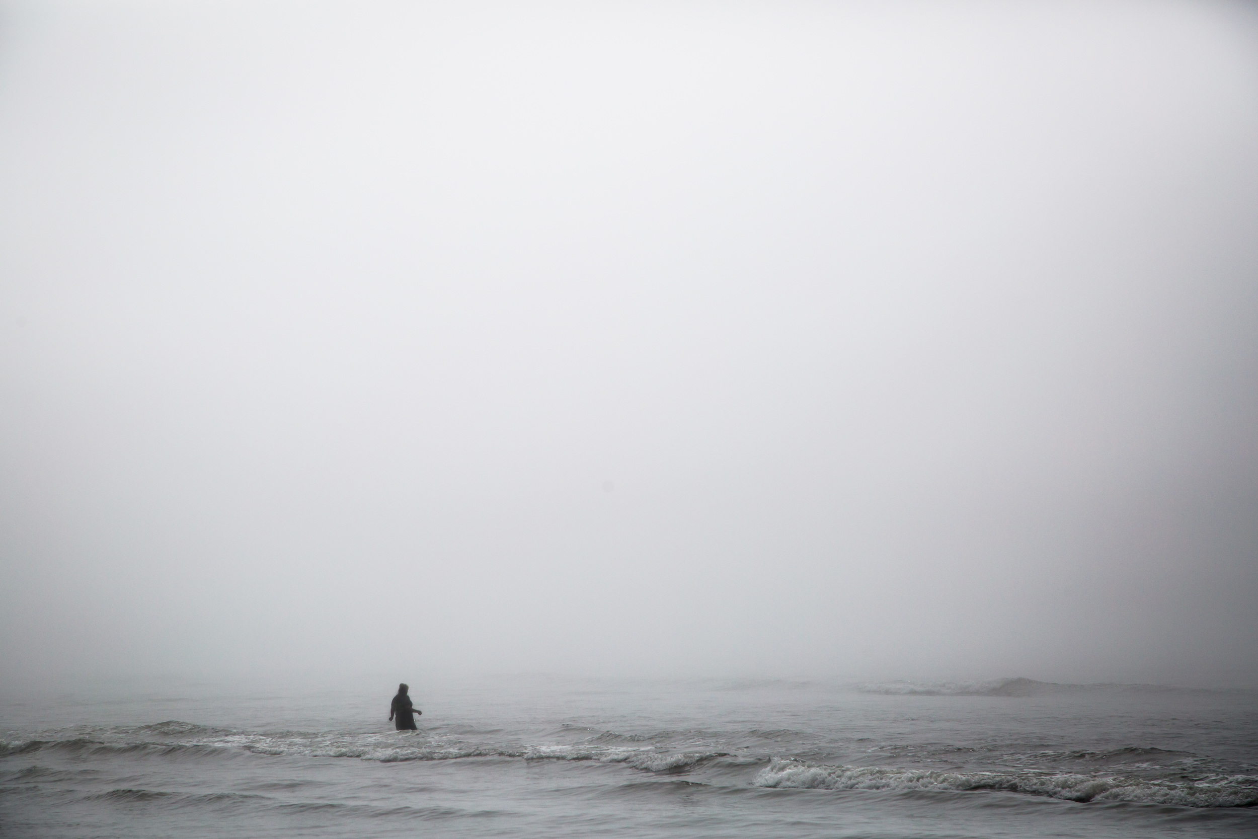 A very foggy day nearly consumes the figure of a person wading into the waves at Kalaloch Beach on August 28, 2015.