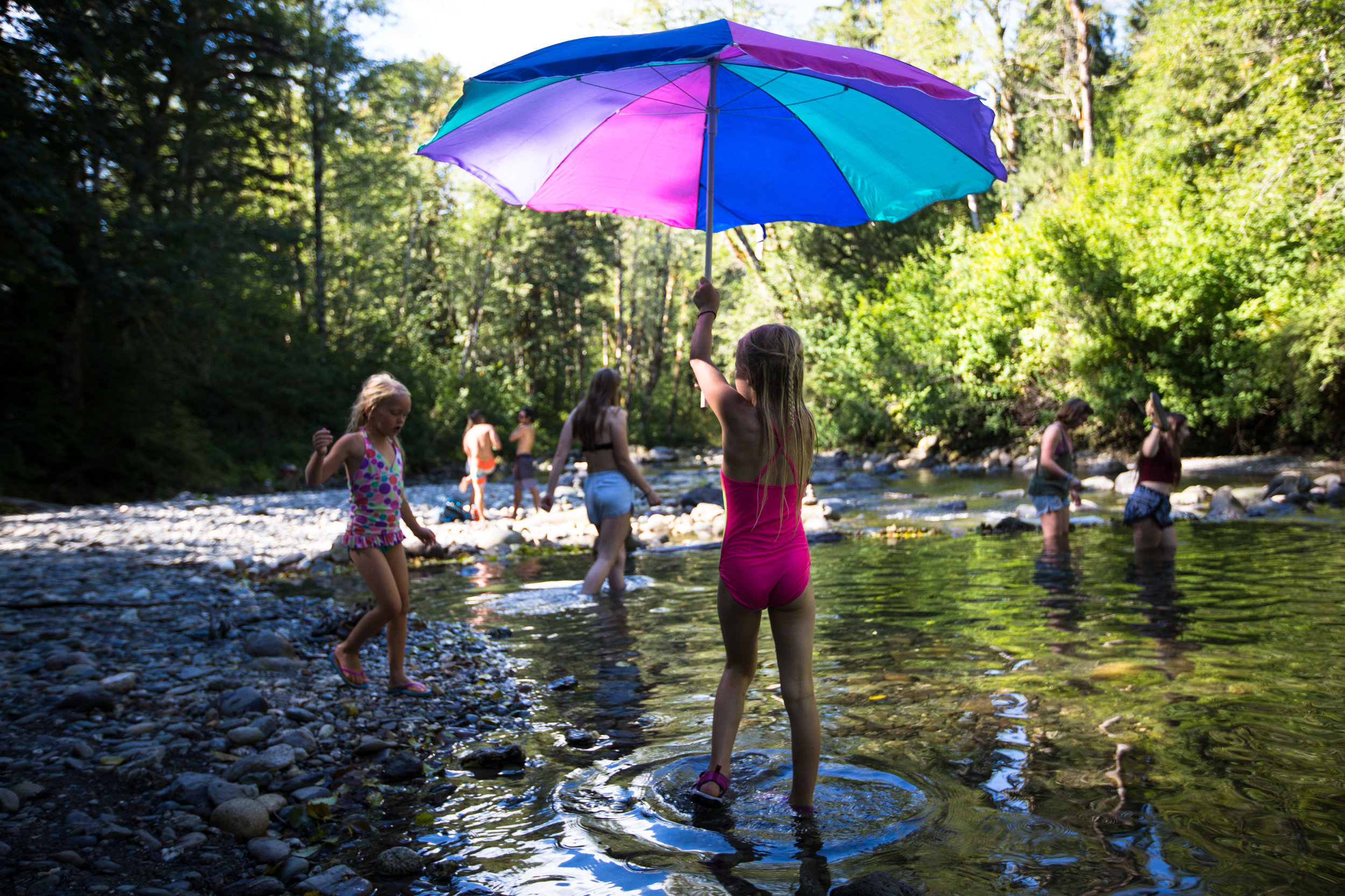 Lily Fronterhouse, 8, holds up an umbrella before wading into the river with her 7-year-old sister Hayley as day one of Summer Meltdown kicks off on Thursday, Aug. 11, 2016 in Darrington, Wa. The annual music festival runs four days with live music, art installations, workshops and on-site camping for attendants.