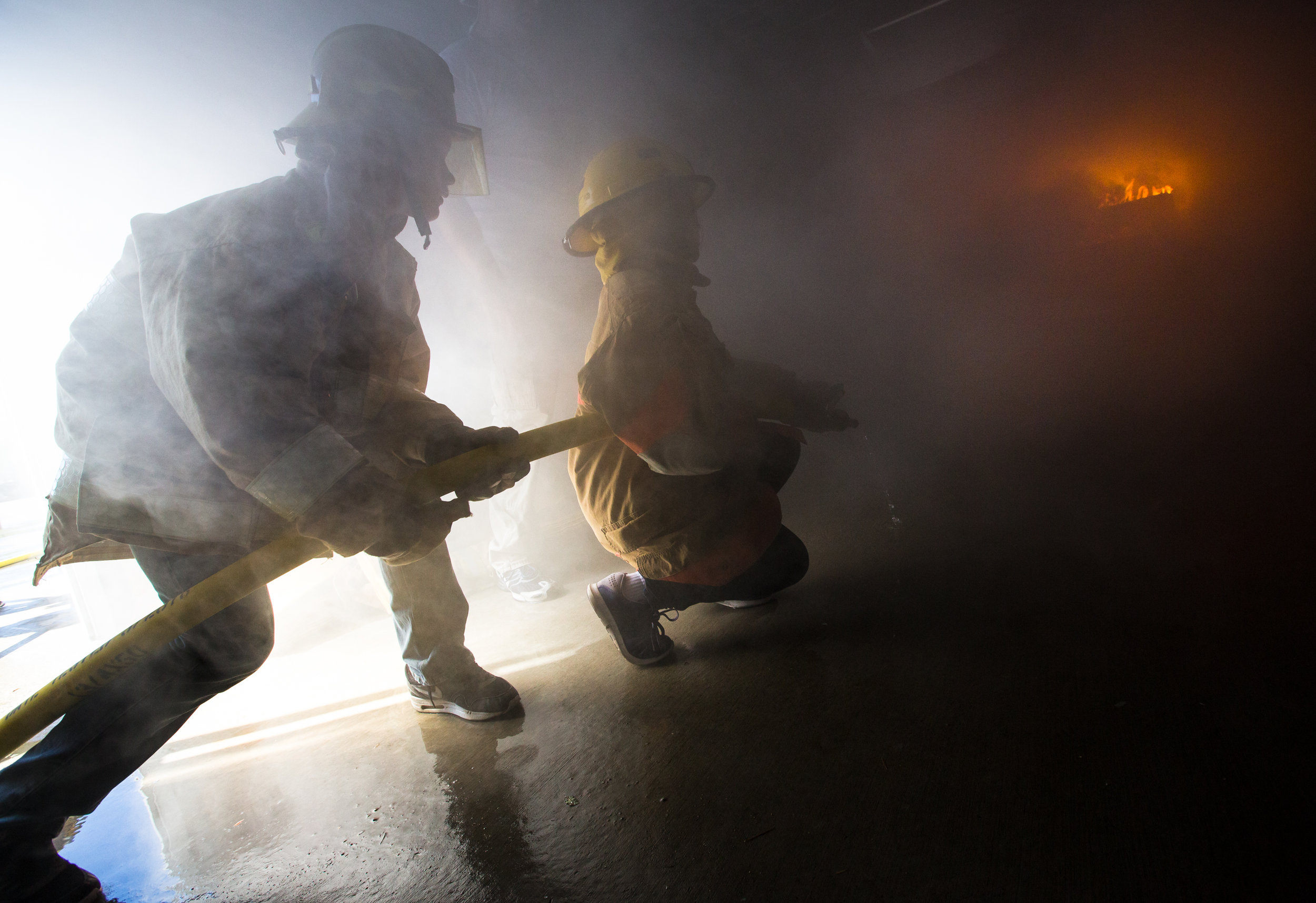 Jake Skogman, 11, (left) and Sarah Anderson, 12, prepare to put out a building fire during the Lynnwood Kids Fire Camp on Thursday. Members of the Lynnwood Fire Department organize group activities for the kids that promote teamwork, including a ladder walk, extinguishing fires and saving a life with ropes.