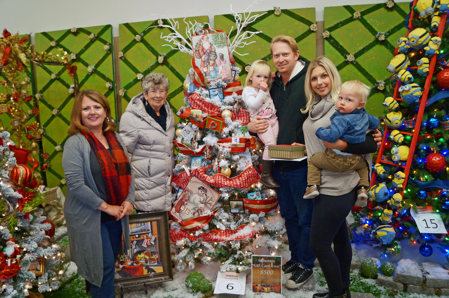 HFHIV Executive Director Tammy Marine and CTL Chairperson Vicki Puterbaugh stand with the winning family of the Gift Card Tree.