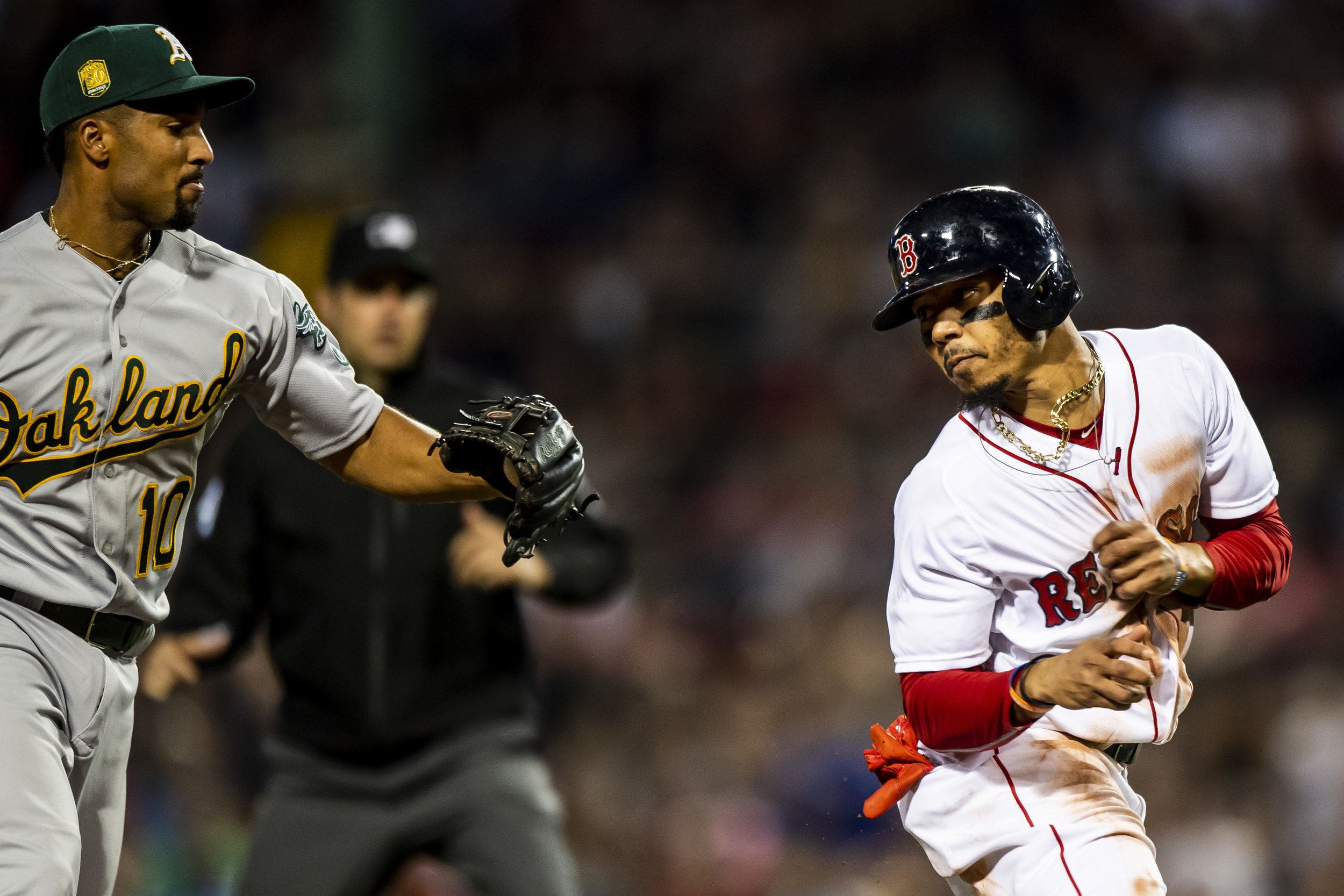May 14, 2018, Boston, MA: Boston Red Sox outfielder Mookie Betts tries to avoid a tag in-between second base and third base in a rundown as the Boston Red Sox face the Oakland Athletics at Fenway Park in Boston, Massachusetts Monday, May 14, 2018. (Photo by Matthew Thomas/Boston Red Sox)