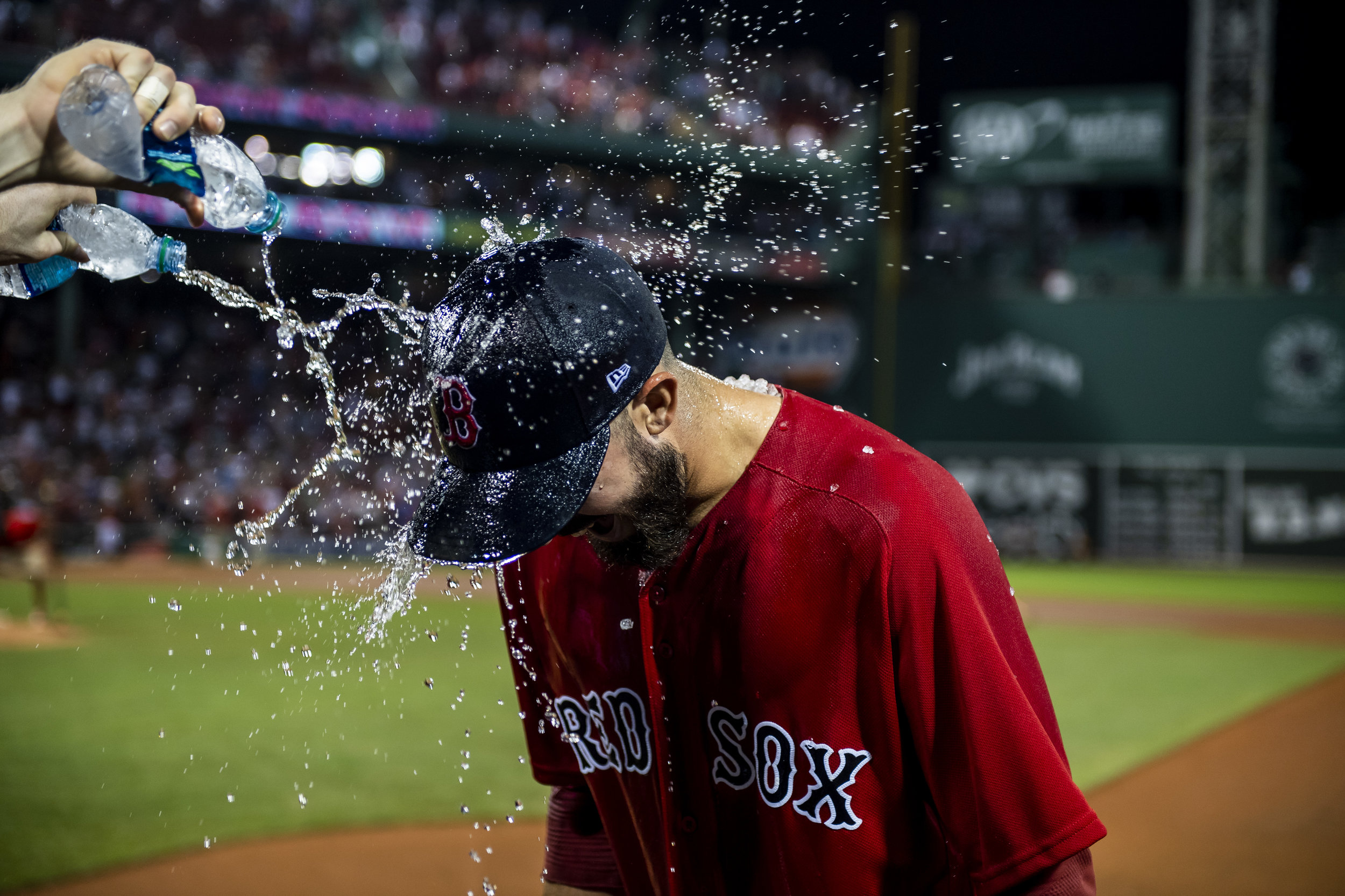 August 3, 2018, Boston, MA: Boston Red Sox outfielder Brock Holt dumps two water bottles on Boston Red Sox pitcher Rick Porcello after the Boston Red Sox defeated the New York Yankees at Fenway Park in Boston, Massachusetts on Friday, August 3, 2018. (Photo by Matthew Thomas/Boston Red Sox)