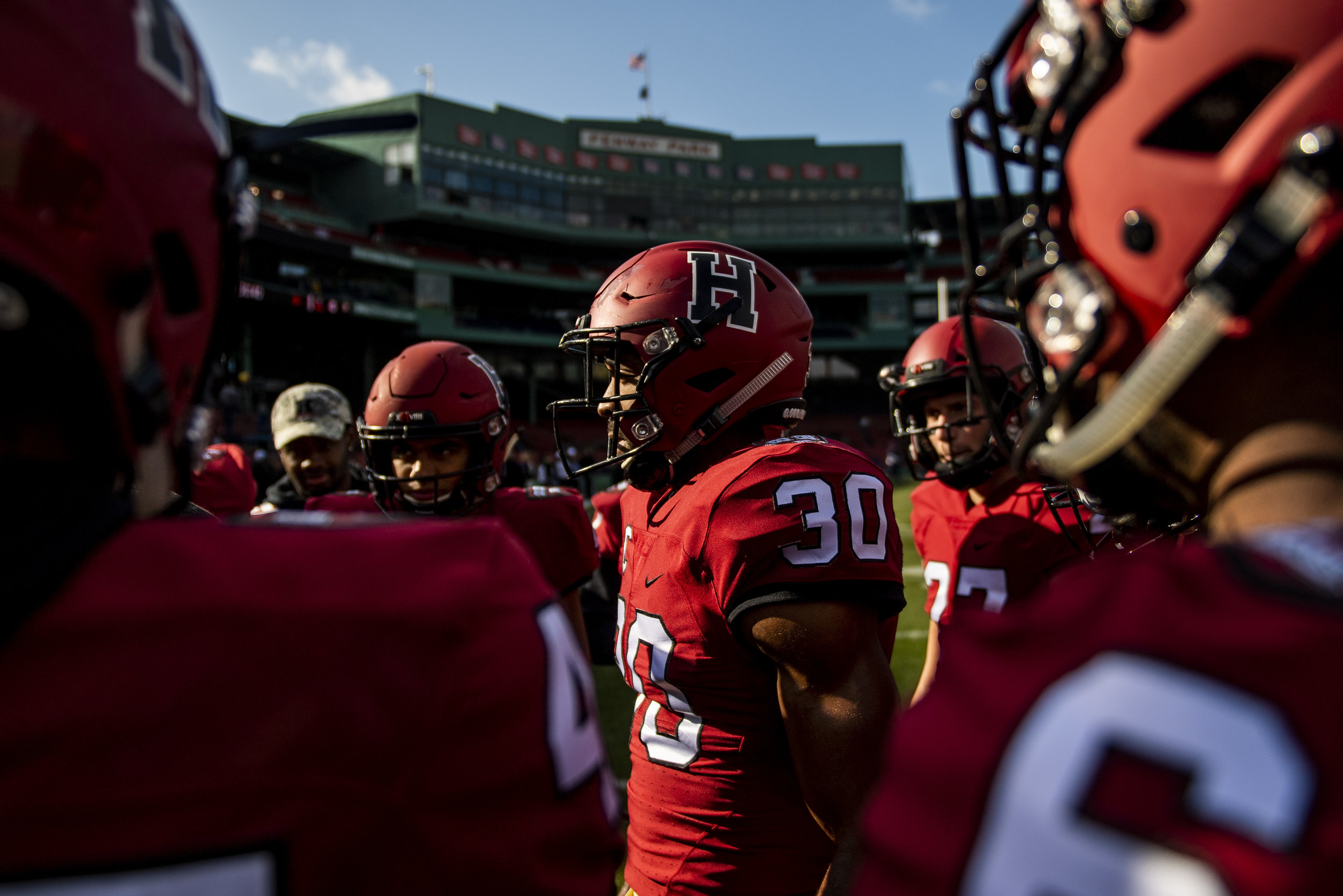 November 16, 2018, Boston, MA: Members of the Harvard football team in a pregame huddle before facing Yale at Fenway Park in Boston, Massachusetts on Thursday, November 16, 2018. (Photo by Matthew Thomas/Boston Red Sox)