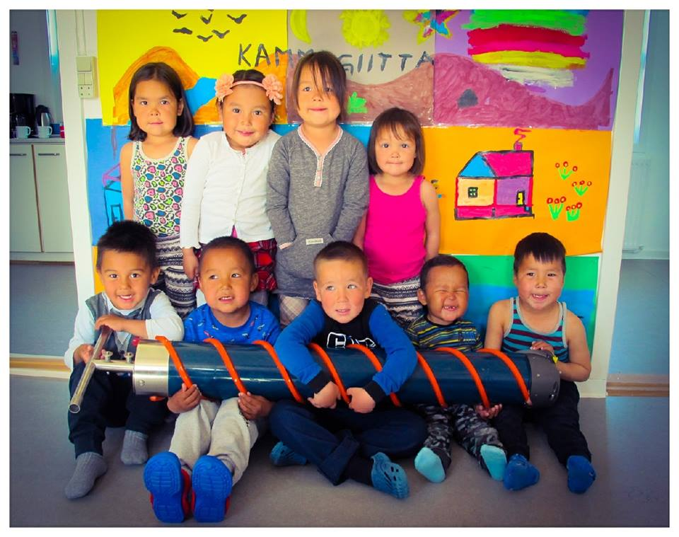 Preschool Kulusuk, Greenland  - During the 2017 summer research mission to Greenland, GEaR's John Bradleyvisited a preschool in Kulusuk to share our work with the community. Using a PowerPoint presentation, and with the assistance of an interpreter, John captivated the children with the story of the Duck and GEaR's efforts to find her.John surprised the children by bringing in our Kovacs Mark V coring system - which they were able to take apart and put back together again. The eager students treated John to a very long and engaging Q&A session, and then sat for this group photo.August 16, 2017001.