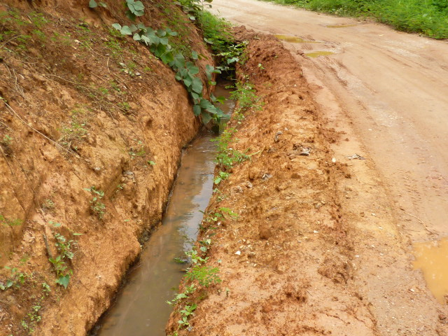 Water flowing in the repaired irrigation channel running along the road