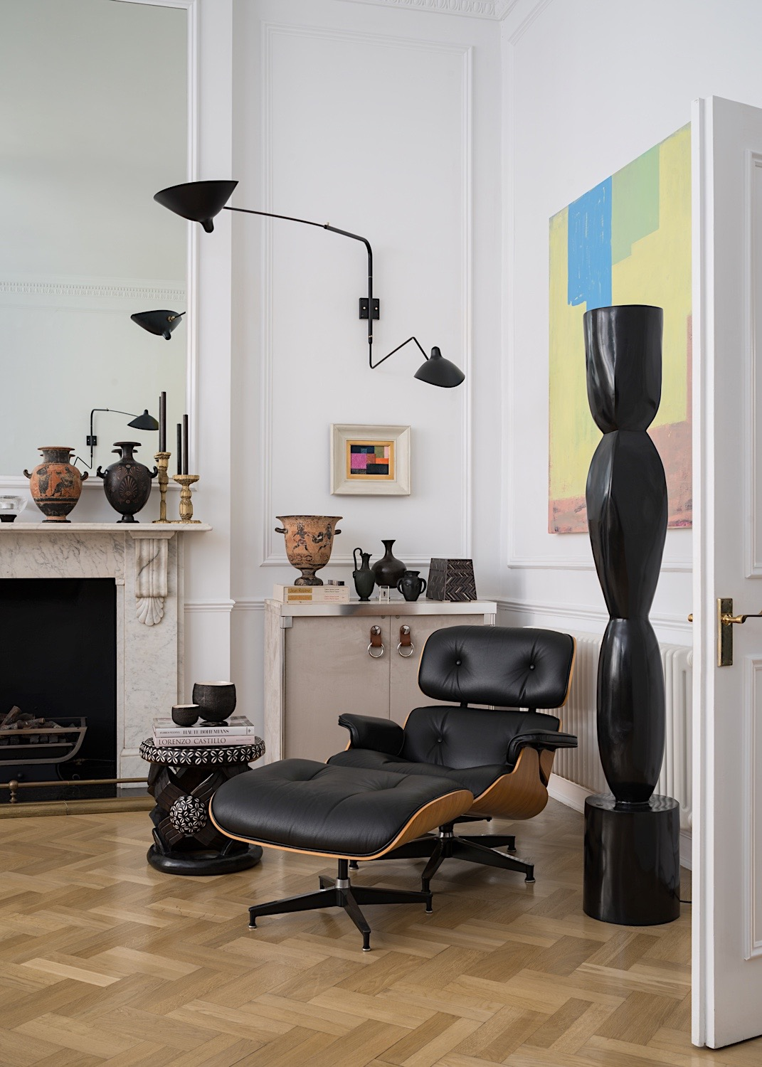 Eames chair & ottoman, Tribal stool, Serge Mouille wall light, bronze torchere by Alexander Lamont. Painting by Joseph Goody.