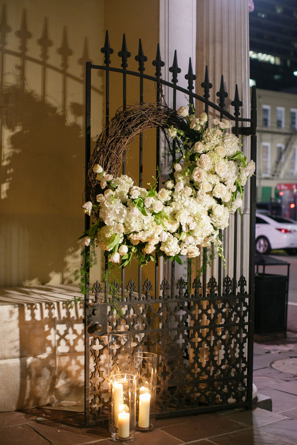 Gate decorations at the New Orleans Board of Trade courtyard entrance | Wrought iron gate floral decor | How to transform an open ballroom with stunning decor | Sapphire Events | Greer G Photography | Board of Trade | White and Gold Wedding | Winter Wedding Inspiration | White and Green Wedding | Ballroom wedding