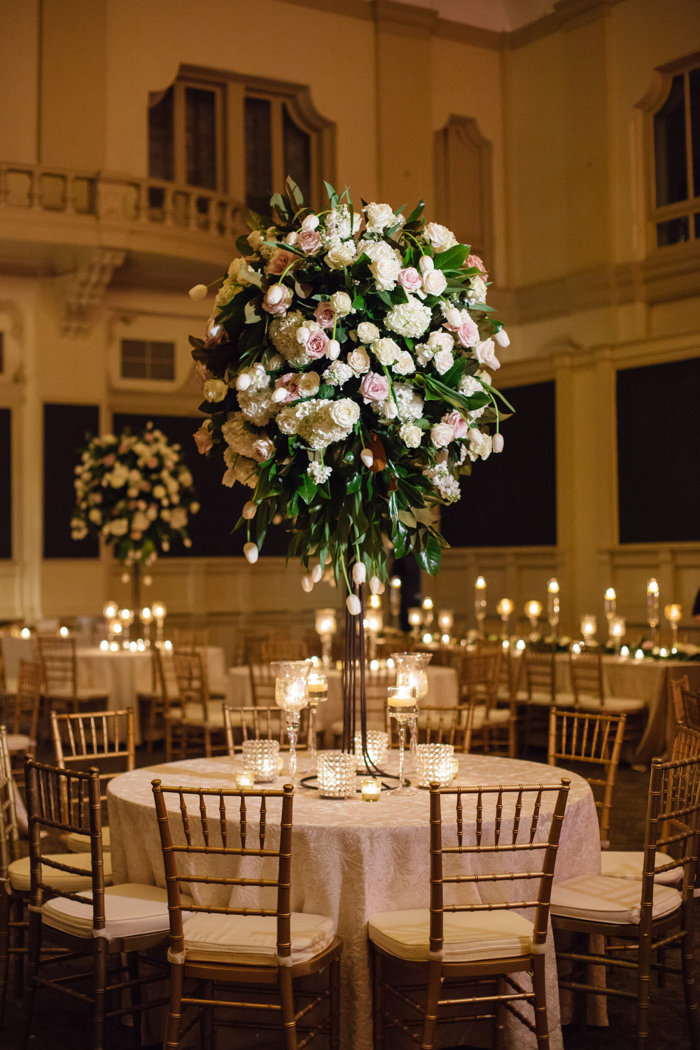 How to transform an open ballroom with stunning decor | Sapphire Events | Greer G Photography | Board of Trade | White and Gold Wedding | Winter Wedding Inspiration | White and Green Wedding | Ballroom wedding | tall floral centerpiece with magnolia leaves