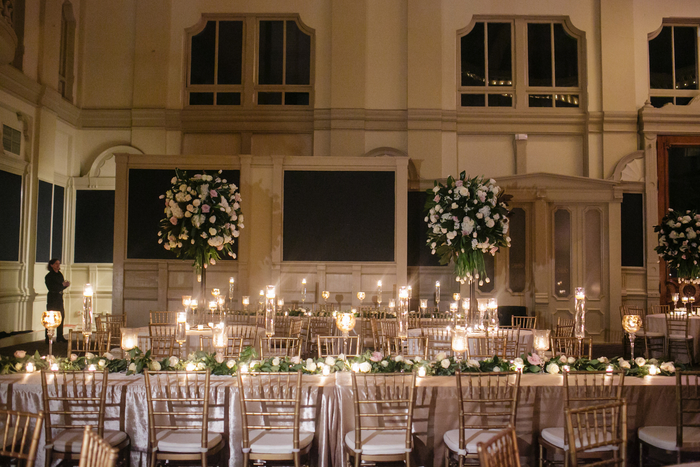 How to transform an open ballroom with stunning decor | Sapphire Events | Greer G Photography | Board of Trade | White and Gold Wedding | Winter Wedding Inspiration | White and Green Wedding | Ballroom wedding | Mix of round and long tables | tall centerpieces with long low garlands