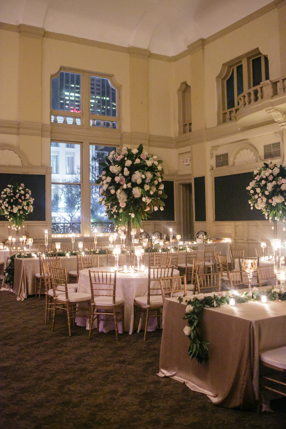 How to transform an open ballroom with stunning decor | Sapphire Events | Greer G Photography | Board of Trade | White and Gold Wedding | Winter Wedding Inspiration | White and Green Wedding | Ballroom wedding | Tall floral centerpieces with magnolia leaves and tulips