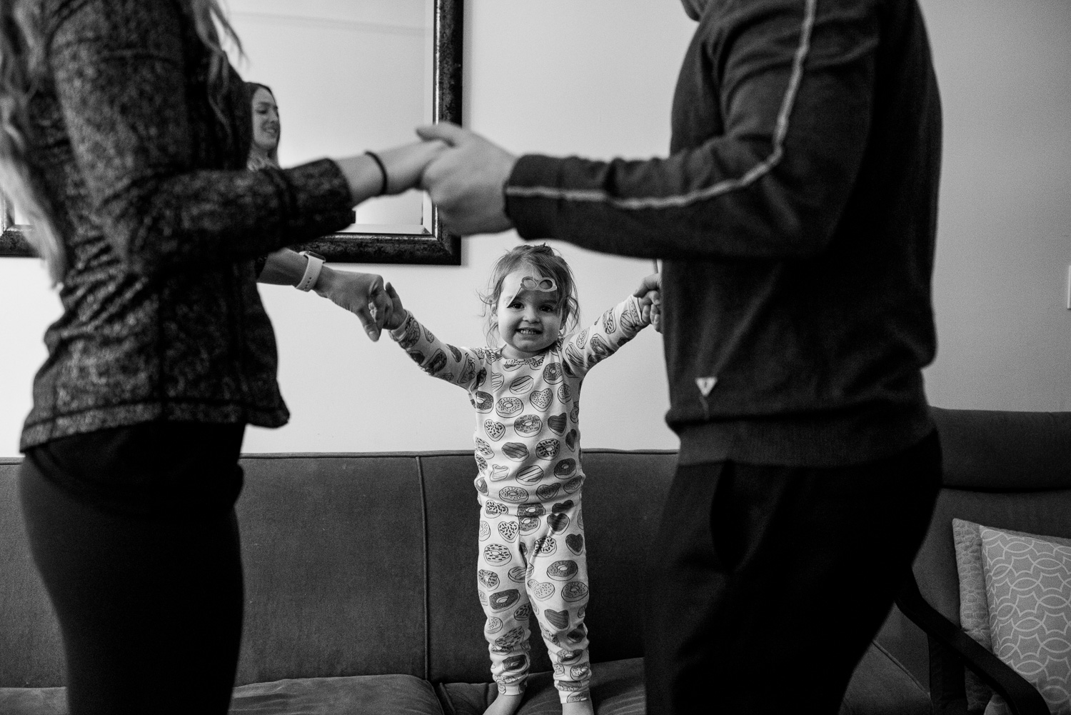 Toddler girl in donut pajamas dances on the couch with her mom and dad