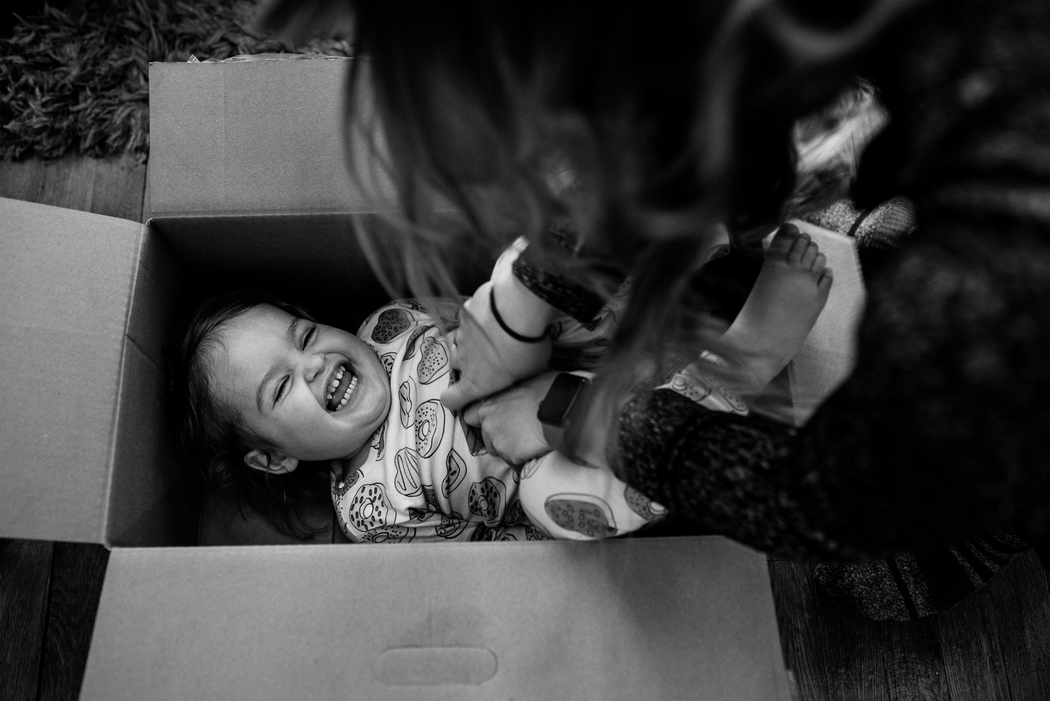 toddler inside a box laughs while being tickled