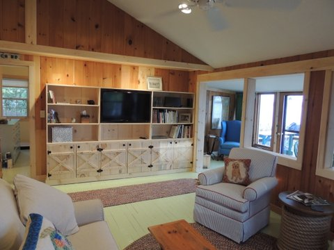 Built ins at this seasonal guest house house the TV, provide storage and a place to display books and family photos.