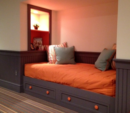 Here is a built in day bed with drawers beneath for storage. Shelves at the end of the bed have an outlet to charge electronic devices.
