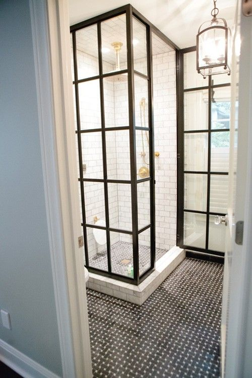Love this small bathroom. The shower is all glass but the steel frame makes it look vintage and industrial. The black basket weave tile looks great next to the marble subway tile.