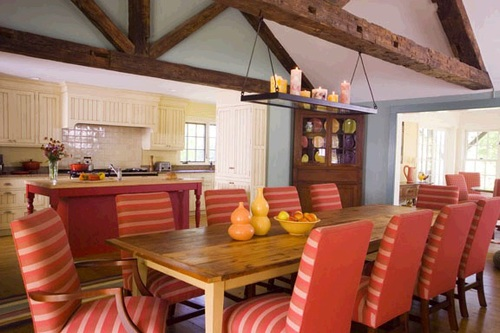 Blood orange backs on these chairs really pops aroundthis custom table.