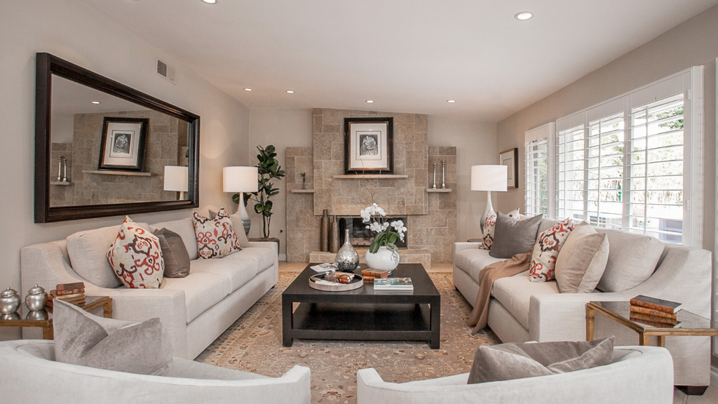 This grand living room's neutral palette is brought to life with just a few throw pillows. Not only do they pop, but notice how they bring out the subtle reds in the rug and warm up the stone fireplace.