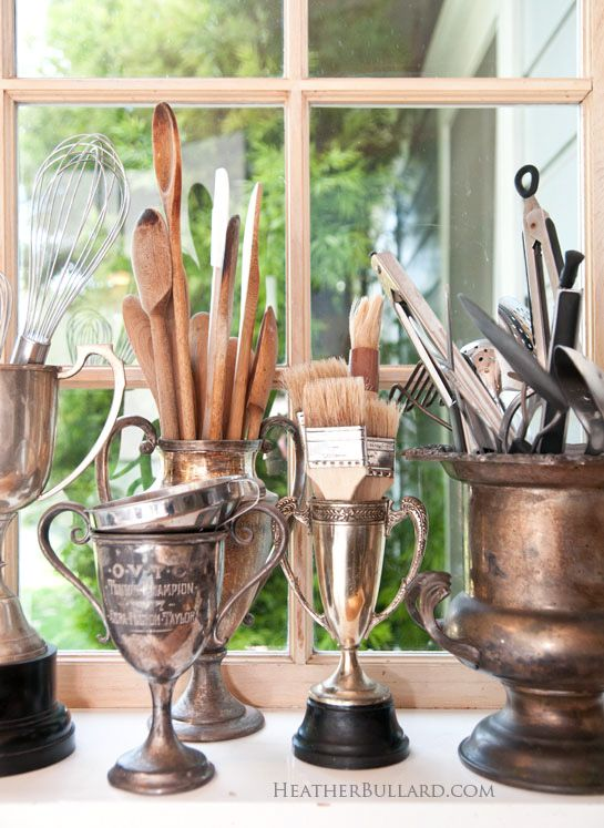 A collection of antique trophy cups serves as a useful display in this kitchen where they hold spoons and other kitchen utensils.