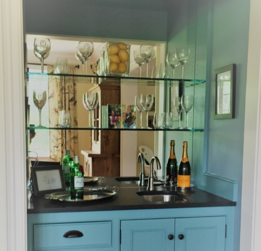 We added mirror glass to the back of this wet bar.  It not only reflects the light, but the objects on the shelves.