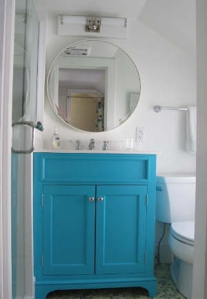 In this tiny bathroom, we selected a bold round mirror with a tiny frame to make the space feel bigger.