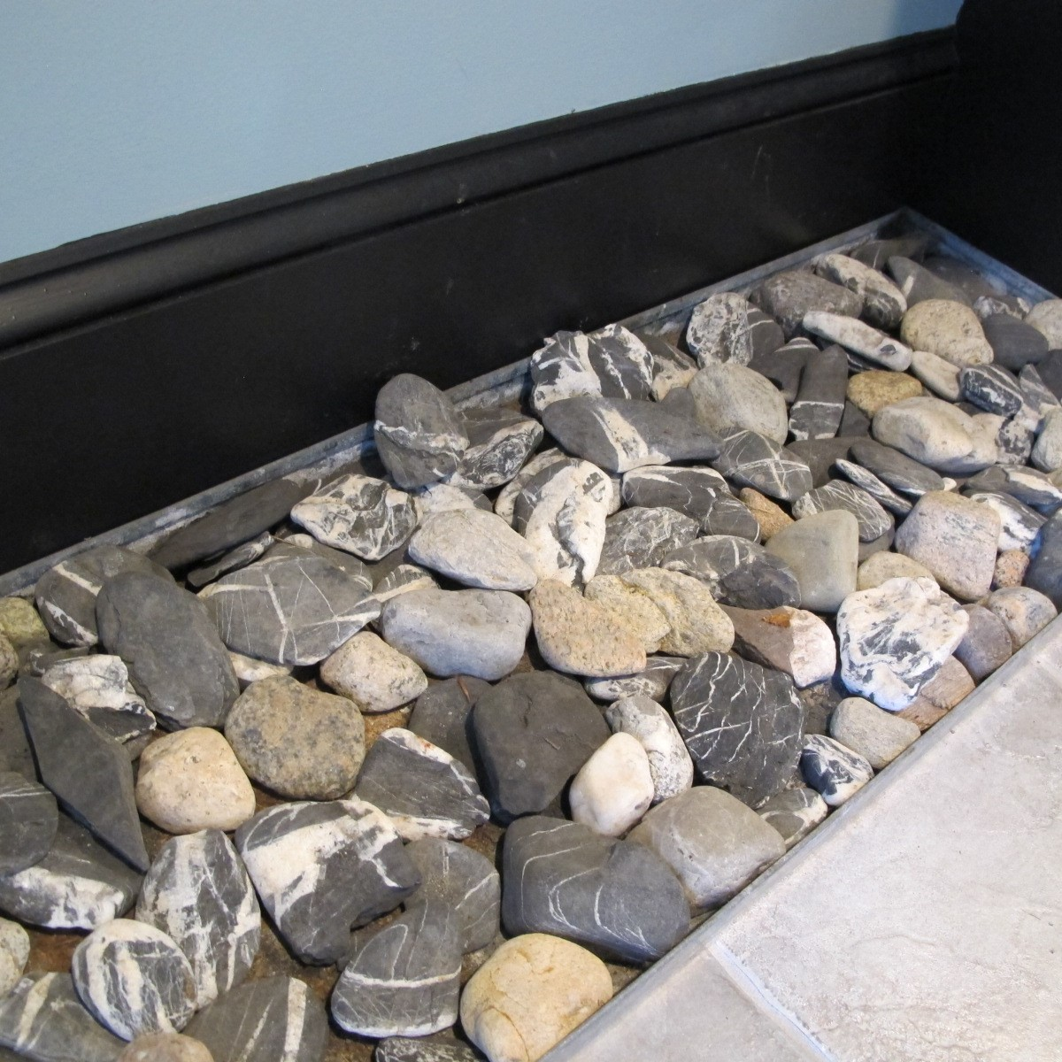 We like to add custom boot trays to our mudrooms.  This one is made from galvanized sheet metal and filled with rocks from locations important to the owners.  The rocks can handle all the mud and salt cast off from the boots while serving as tokens from past adventures.