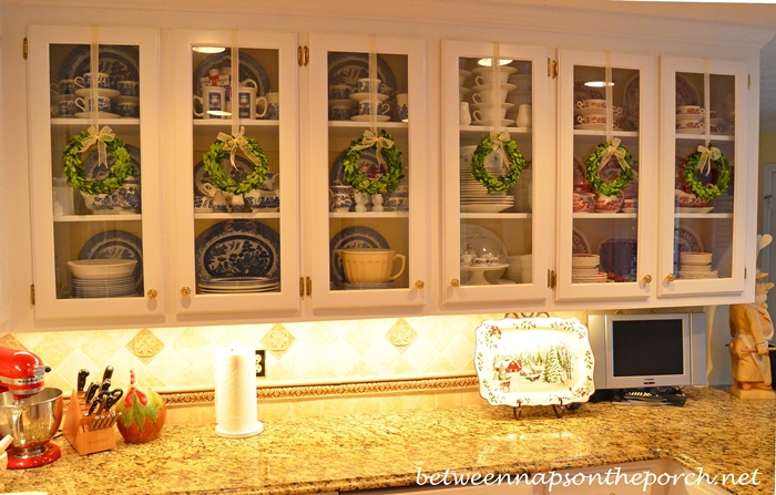 This image gave me the idea to remake the burnt out light bulb wreath a bit smaller and hang from the cabinet. These boxwood wreaths are beautiful and came from the blog Between Naps on the Porch.